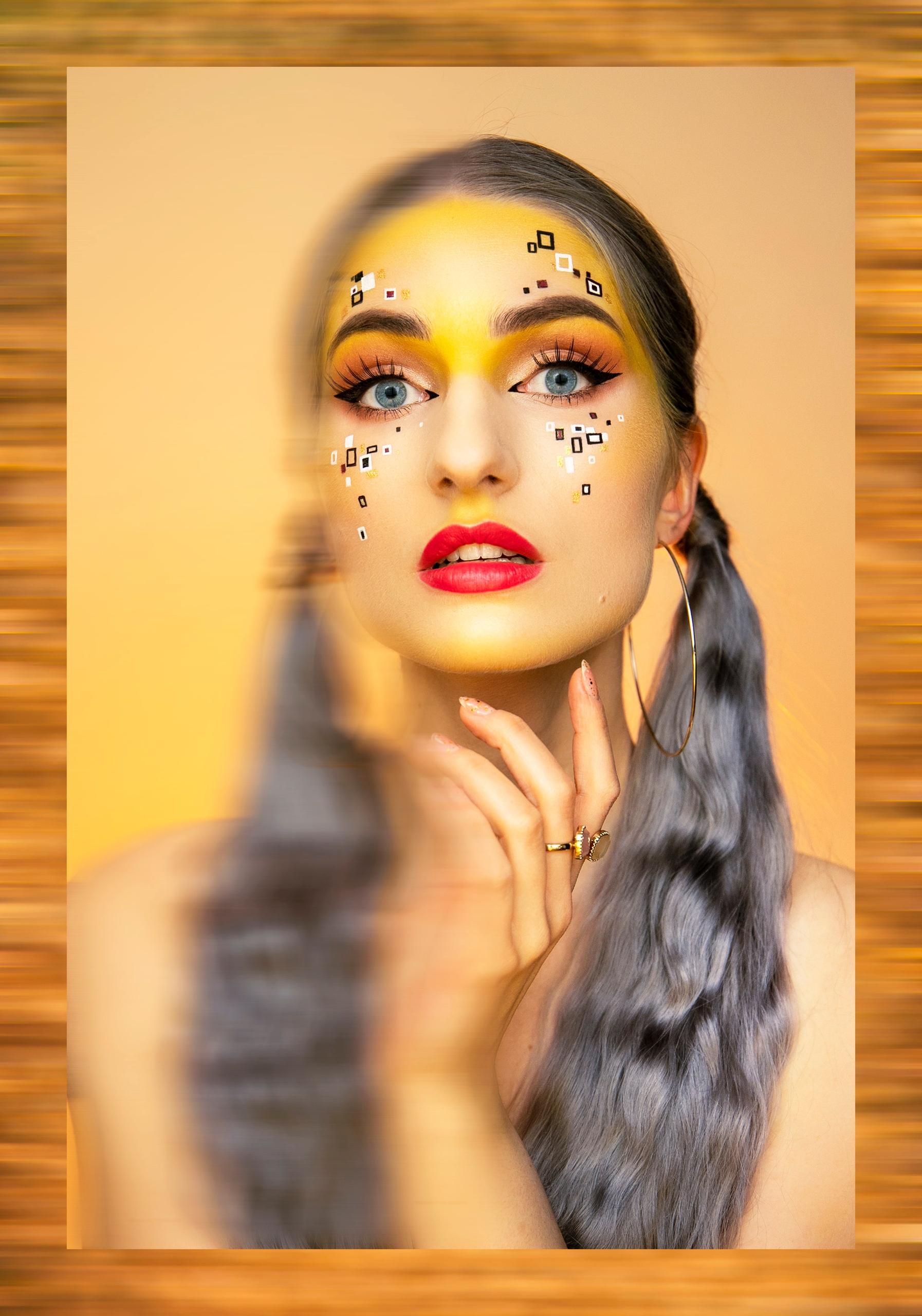 Portret przedstawia kobietę w artystycznym makijażu patrzącą w dal. Dookoła fotografii ramka.