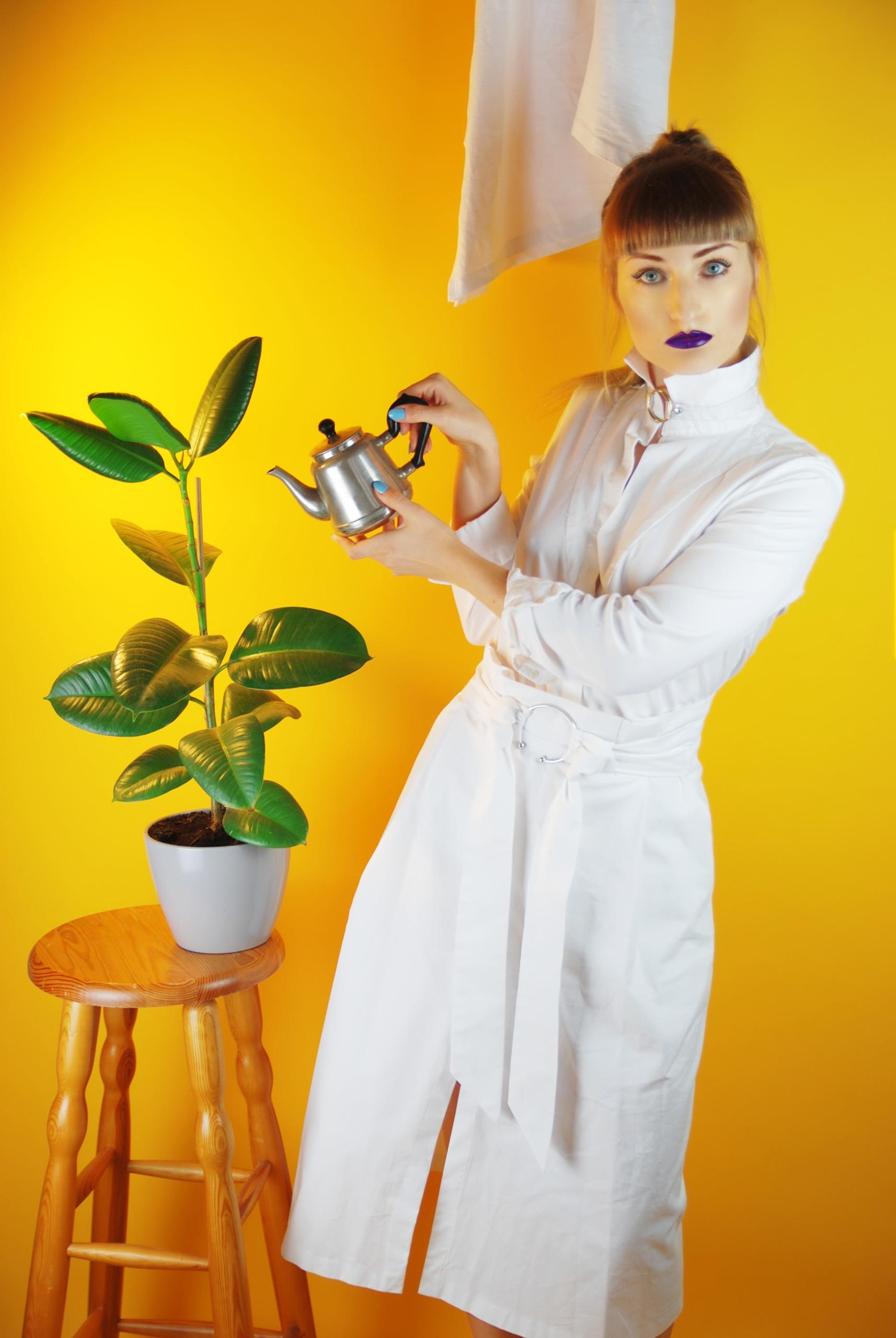 Zdjęcie przedstawia młodą kobietę ubraną na biało ze srebrnym naczyniem w ręce. Kobieta podlewa kwiat znajdujący się z lewej strony na krześle. Tło jest żółte.