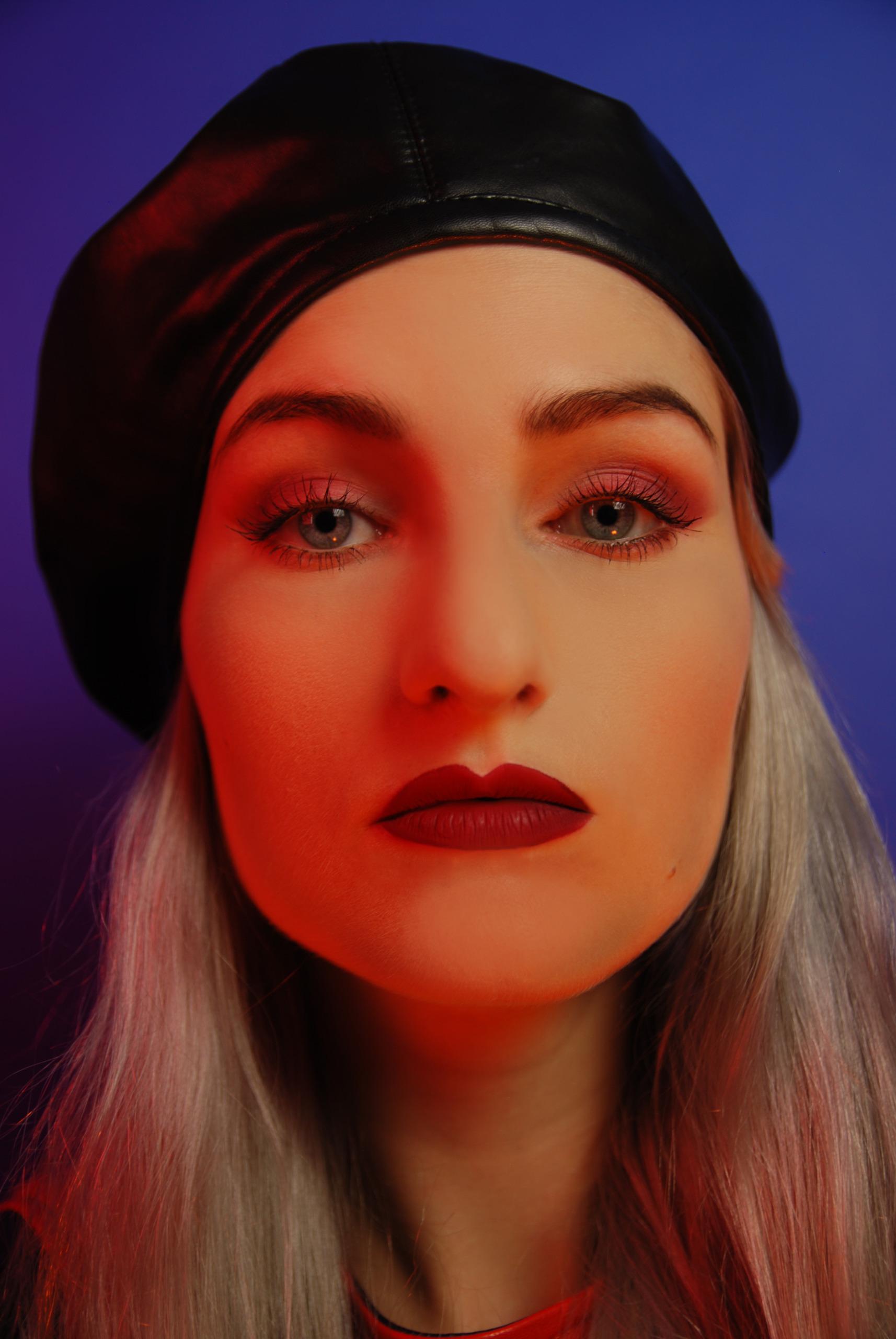 Zdjęcie przedstawia twarz młodej kobiety z jasnoszarymi włosami w czarnym berecie na niebieskim tle. Twarz oświetlona jest czerwonym światłem, całość na niebieskim tle.
