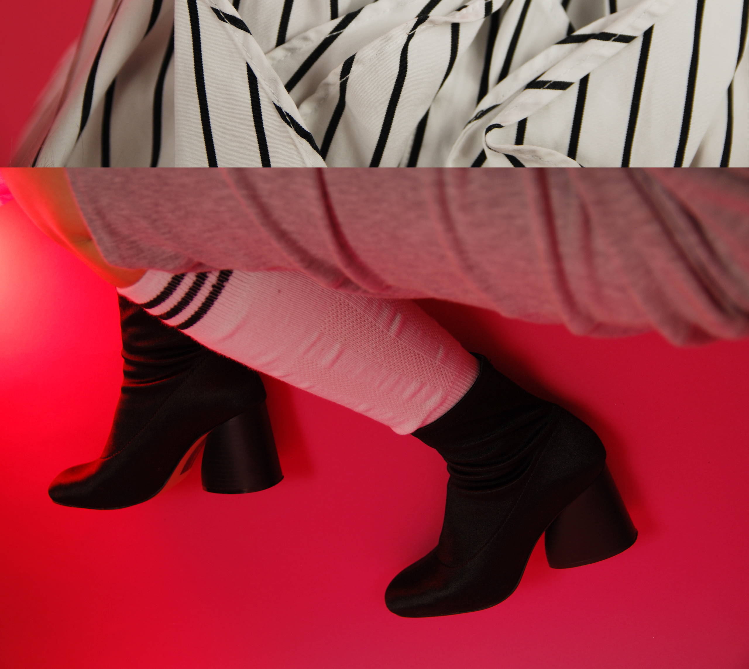 Obraz przedstawia zdjęcie kobiecych nóg w białych skarpetach i czarnych butach, całość na różowym tle. W górnej części zdjęcia widzimy fragment materiału w czarno-białe paski.
