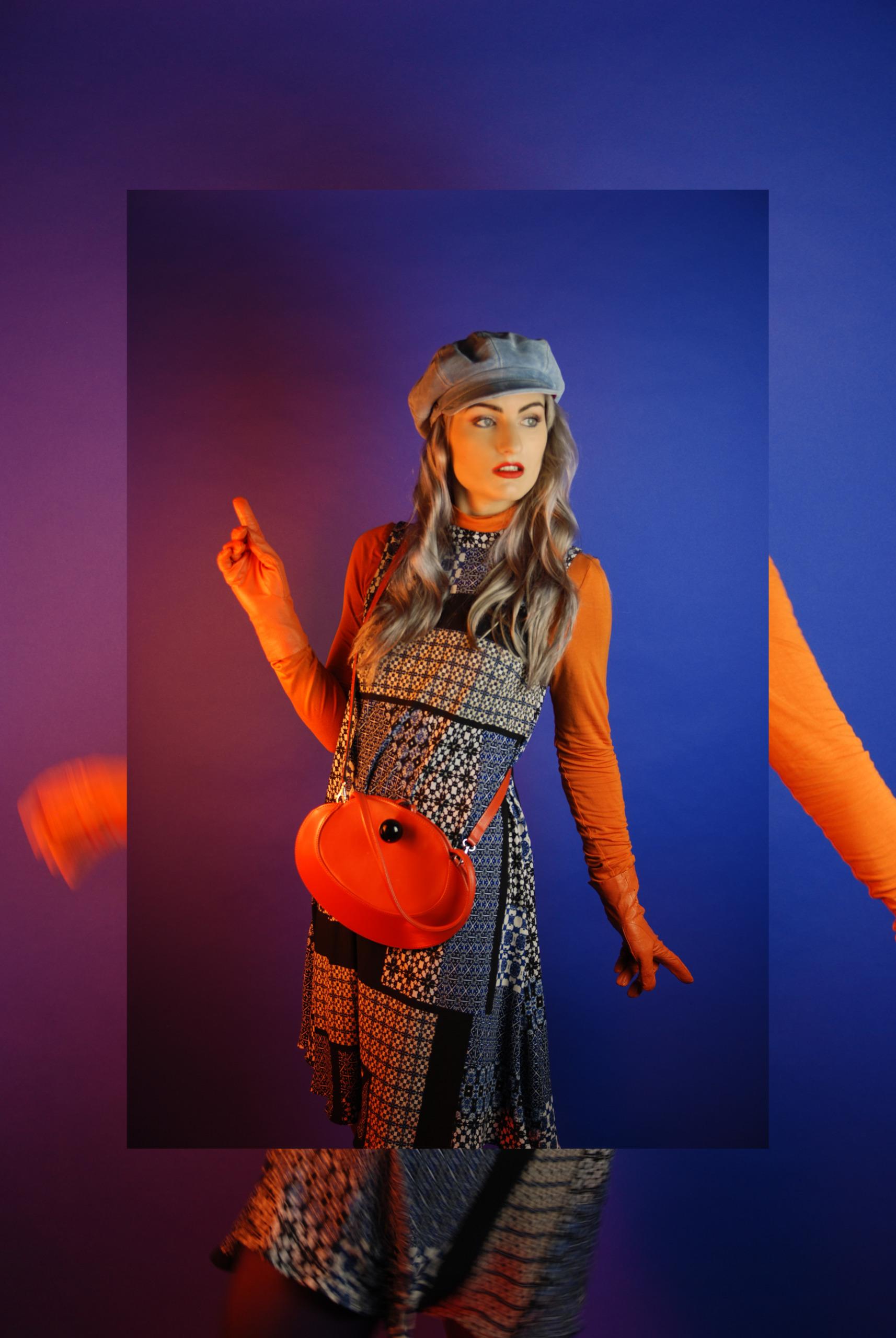 Zdjęcie przedstawia młodą kobietę ubraną w sukienkę, pomarańczową bluzkę, rękawiczki i torebkę w kolorze bluzki, kobieta ma niebieski beret na głowie i patrzy w lewą stronę. Całość na niebieskim tle oświetlonym ciepłym światłem.
