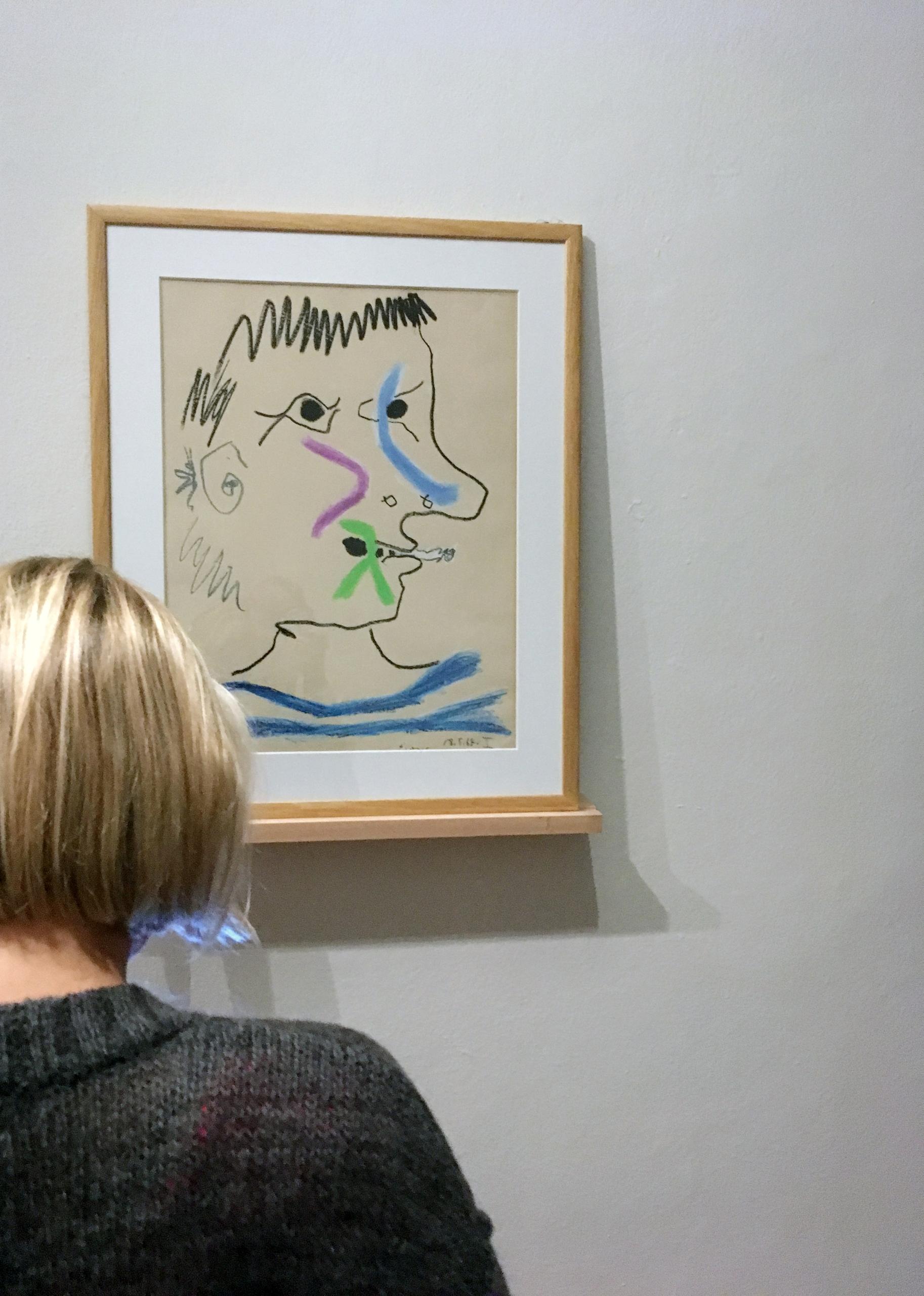 Zdjęcie przedstawia kobietę z krótkimi włosami oglądającą obraz Pabla Picassa.