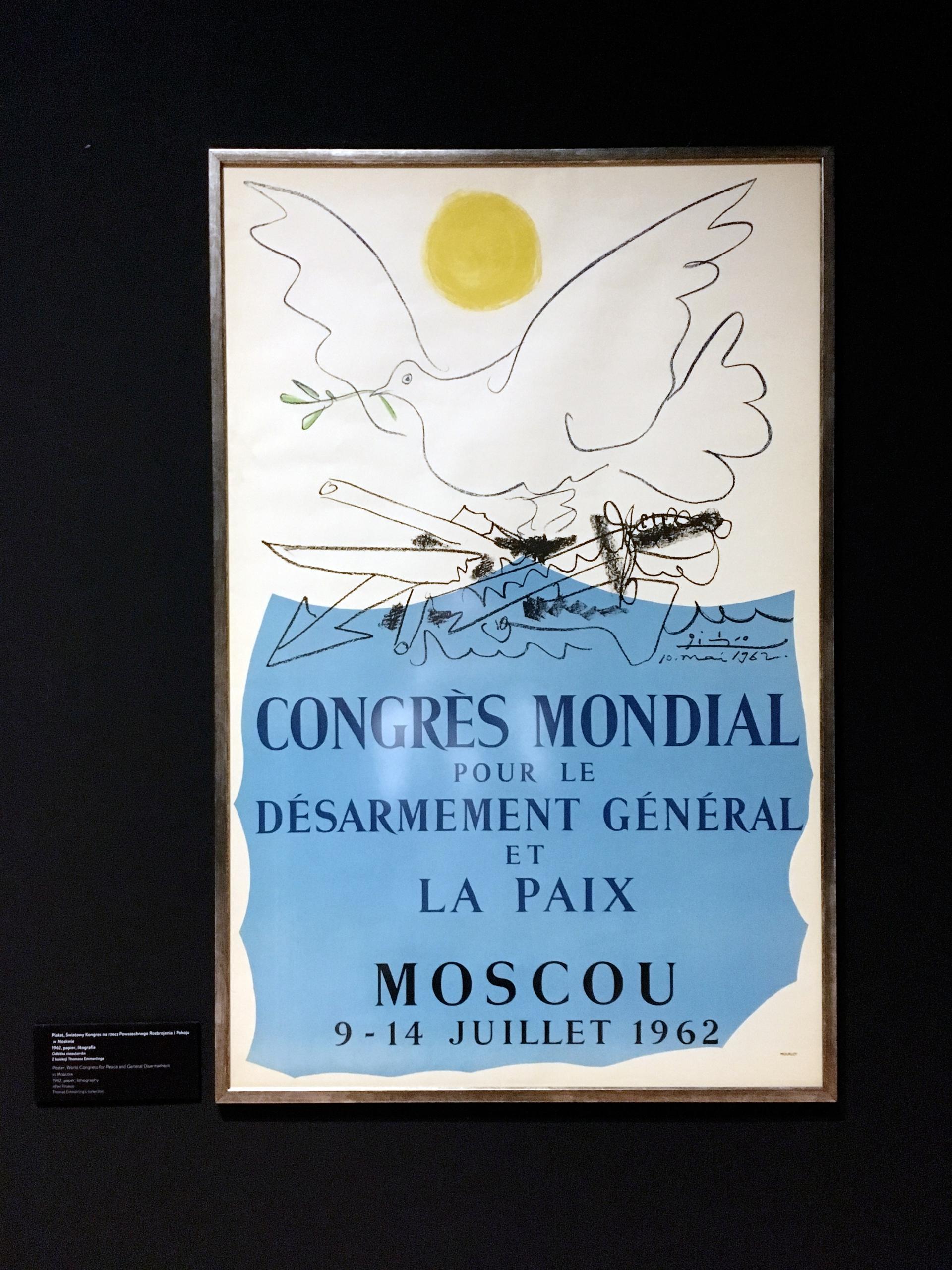 Zdjęcie przedstawia plakat powieszony na czarnej ścianie. Plakat przedstawia gołębia, widzimy kolor niebieski i żółty akcent.