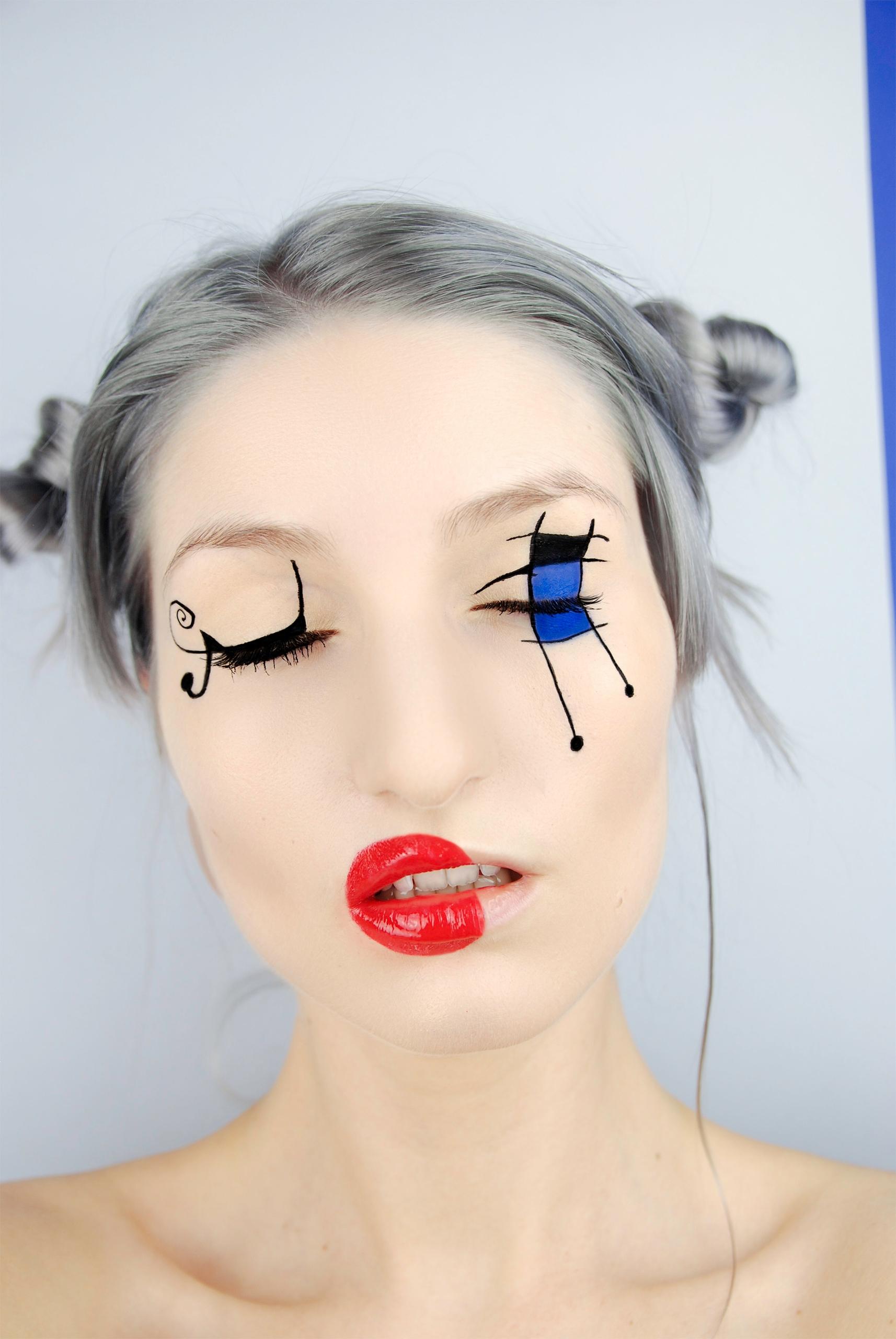 Zdjęcie przedstawia portret młodej kobiety na szarym tle w artystycznym makijażu. Kobieta ma zamknięte oczy i siwe włosy.