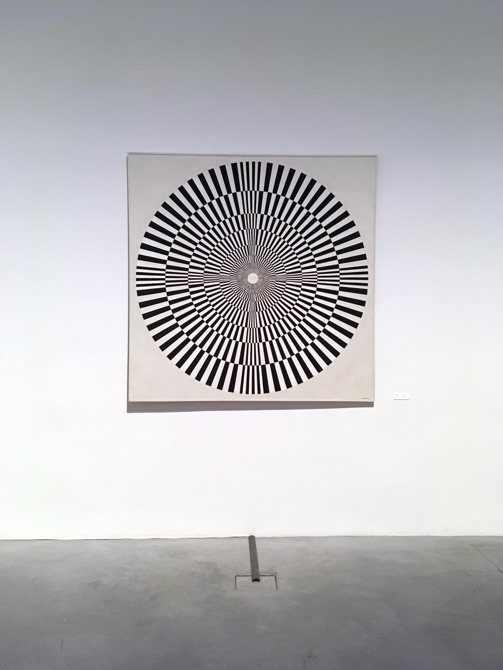 Zdjęcie przedstawia obraz wiszący na białej ścianie. Na obrazie widzimy czarno-białe koło.