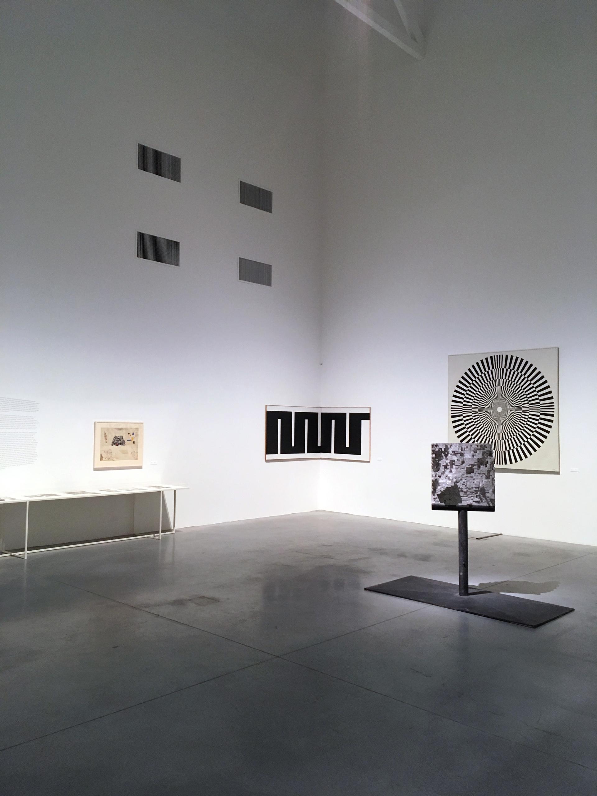Zdjęcie przedstawia pomieszczenie z białymi ścianami. Na ścianach wiszą obrazy, a na podłodze stoją rzeźby.