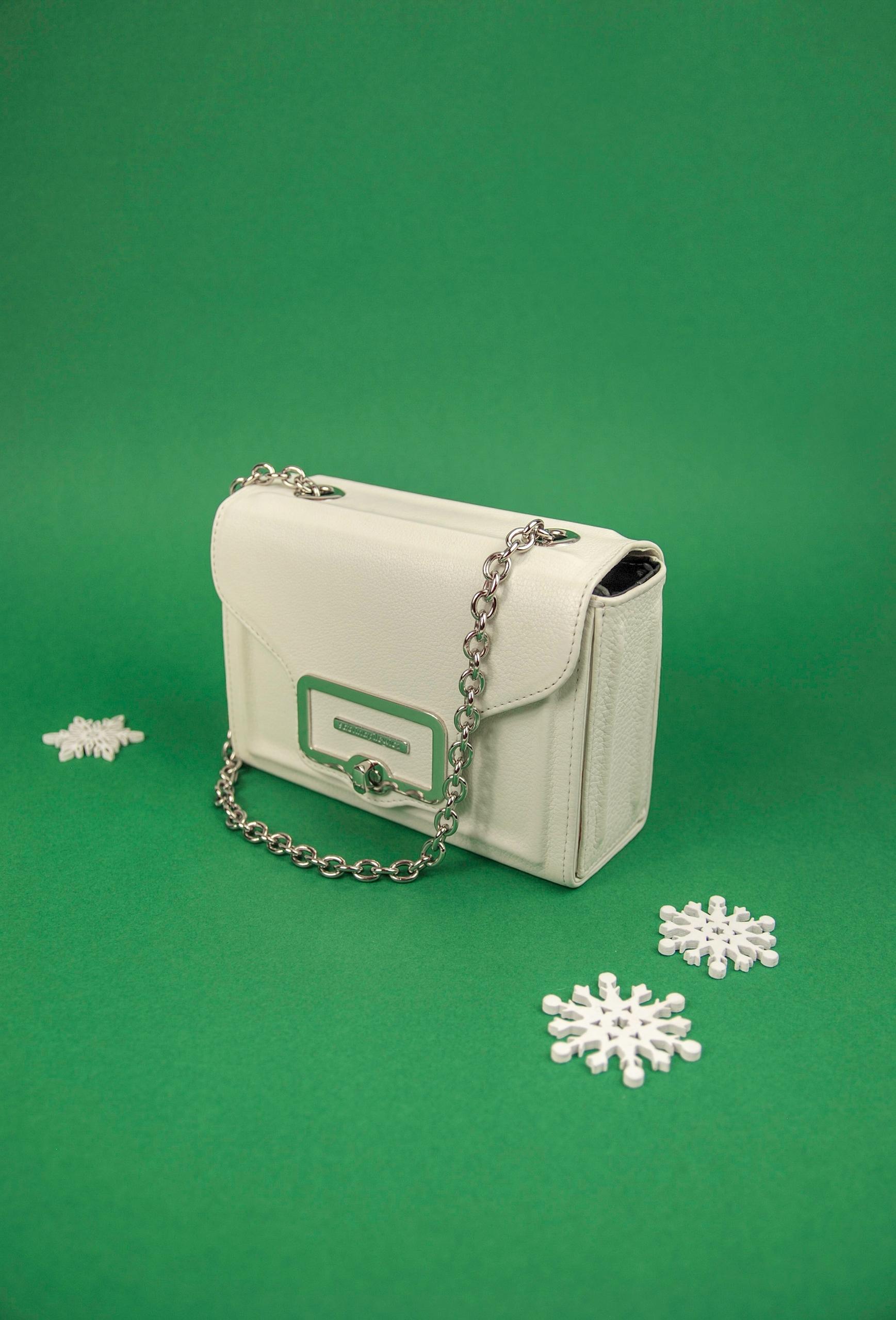 Zdjęcie przedstawia białą małą torebkę na zielonym tle. Obok widzimy trzy białe dekoracyjne elementy w kształcie gwiazdek.