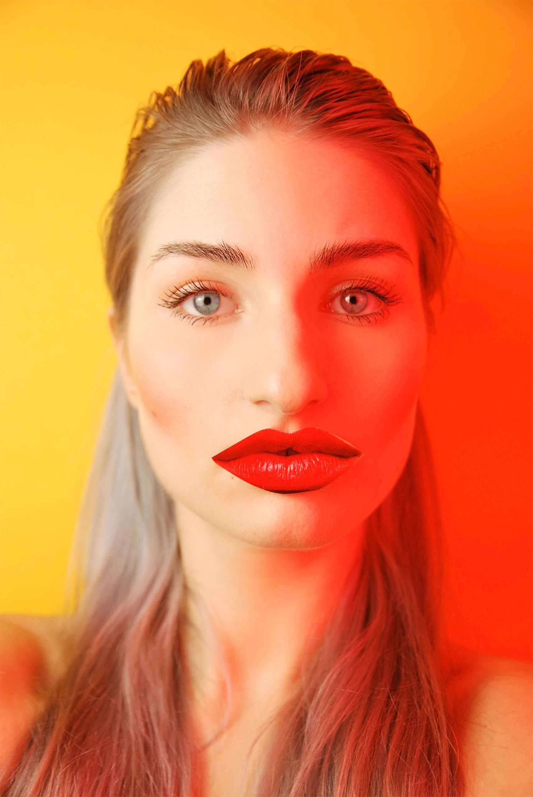 Zdjęcie przedstawia portret kobiety z długimi włosami. Połowę jej twarzy oświetla czerwone światło. Całość na żółtym tle.