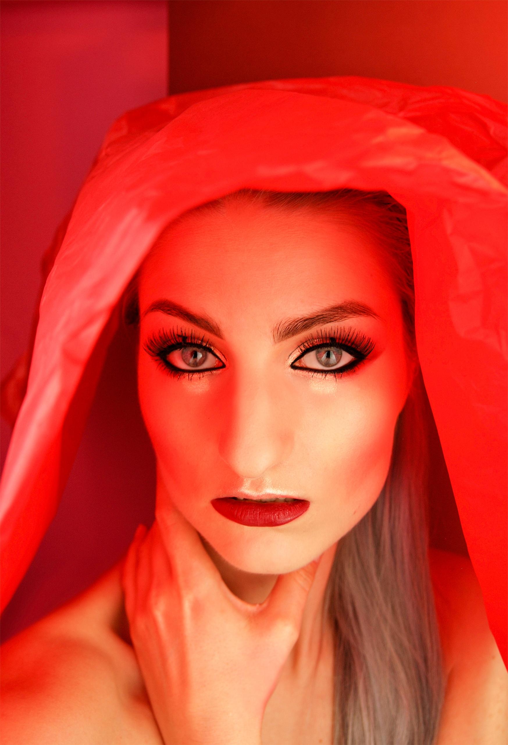 Zdjęcie przedstawia portret młodej kobiety w mocno czerwonym otoczeniu. Kobieta trzyma rękę na szyi i patrzy w obiektyw.
