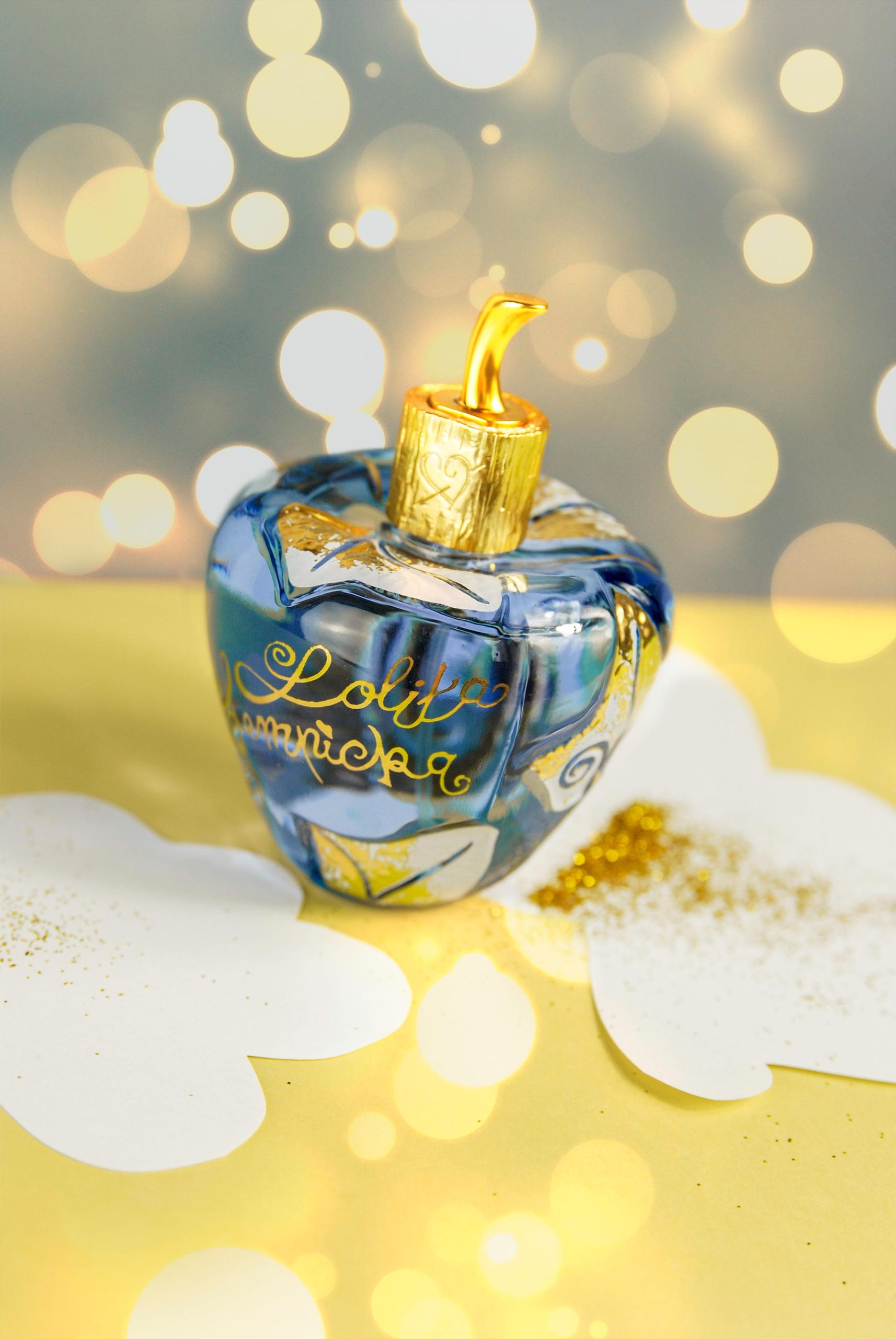 Zdjęcie przedstawia niebieski flakonik perfum ze złotymi elementami. Na zdjęciu widoczne są efekty świetlne.