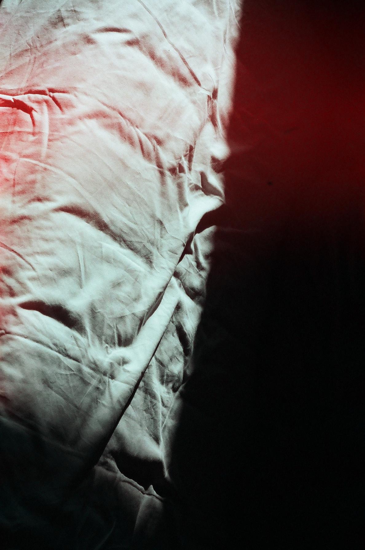 Zdjęcie przedstawia fragment pogniecionej białej tkaniny, na którą pada światło słoneczne.