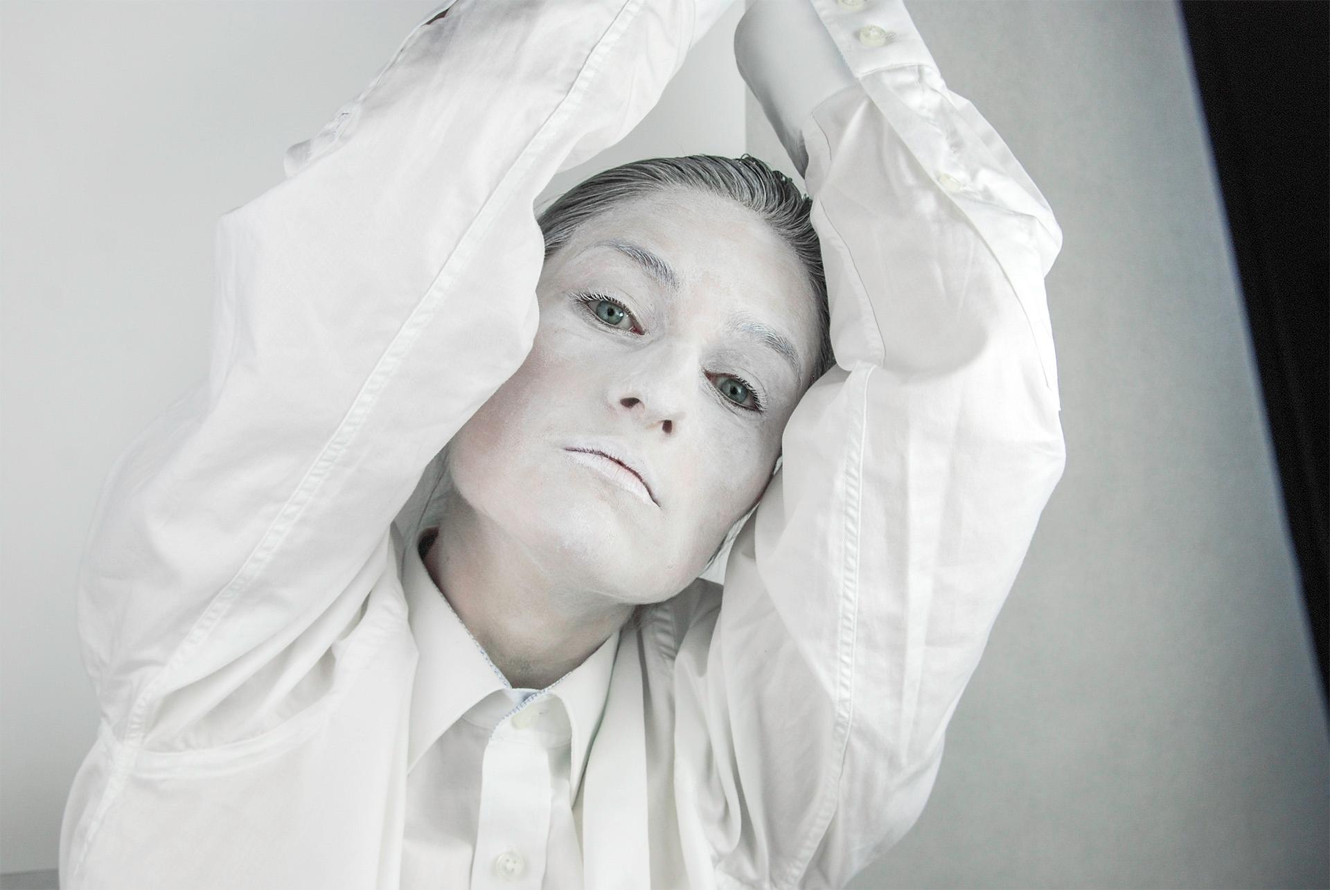 Zdjęcie przedstawia postać pomalowaną na biało z uniesionymi do góry rękami.
