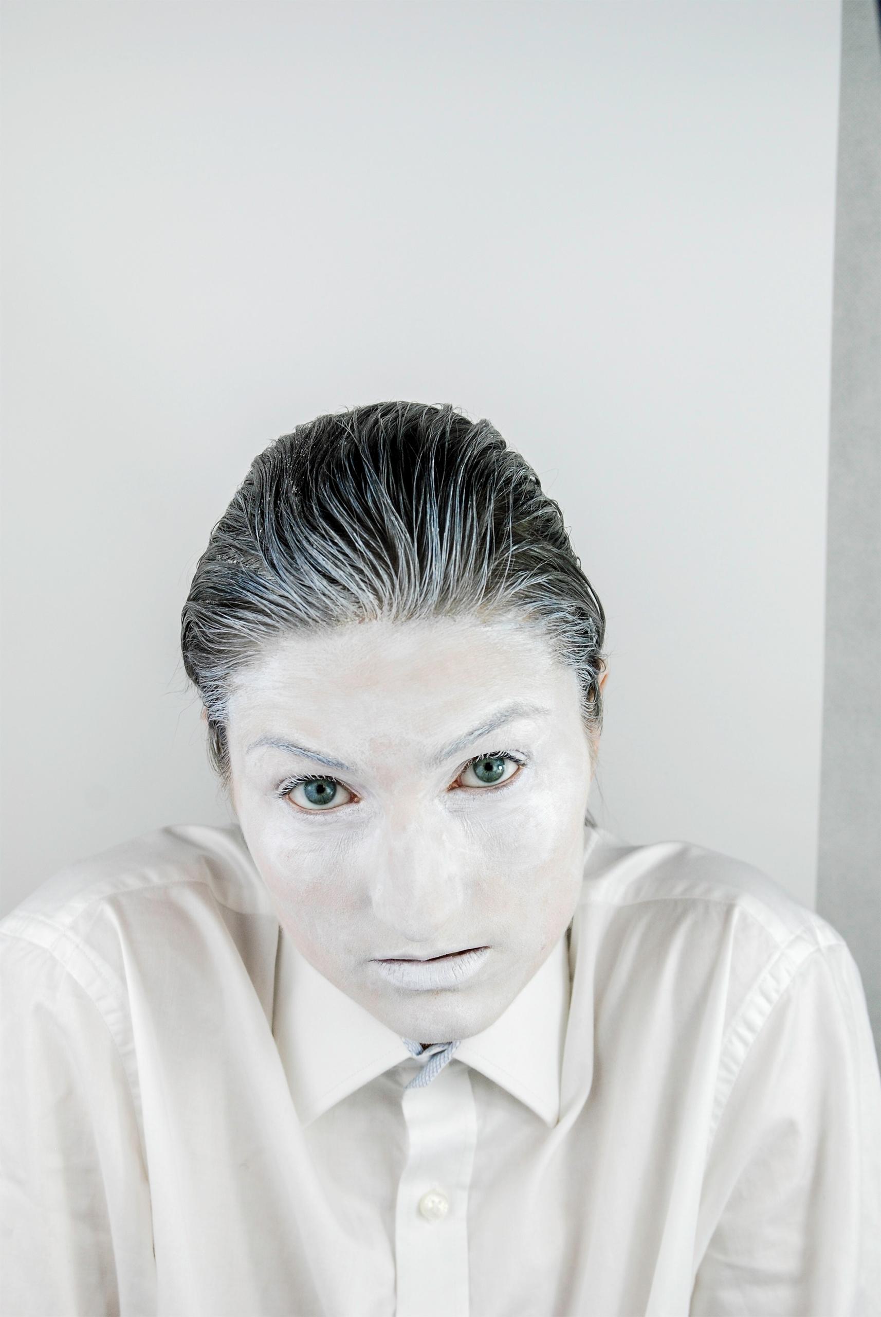 Zdjęcie przedstawia postać pomalowaną na biało w lekko zgarbionej pozycji ciała.