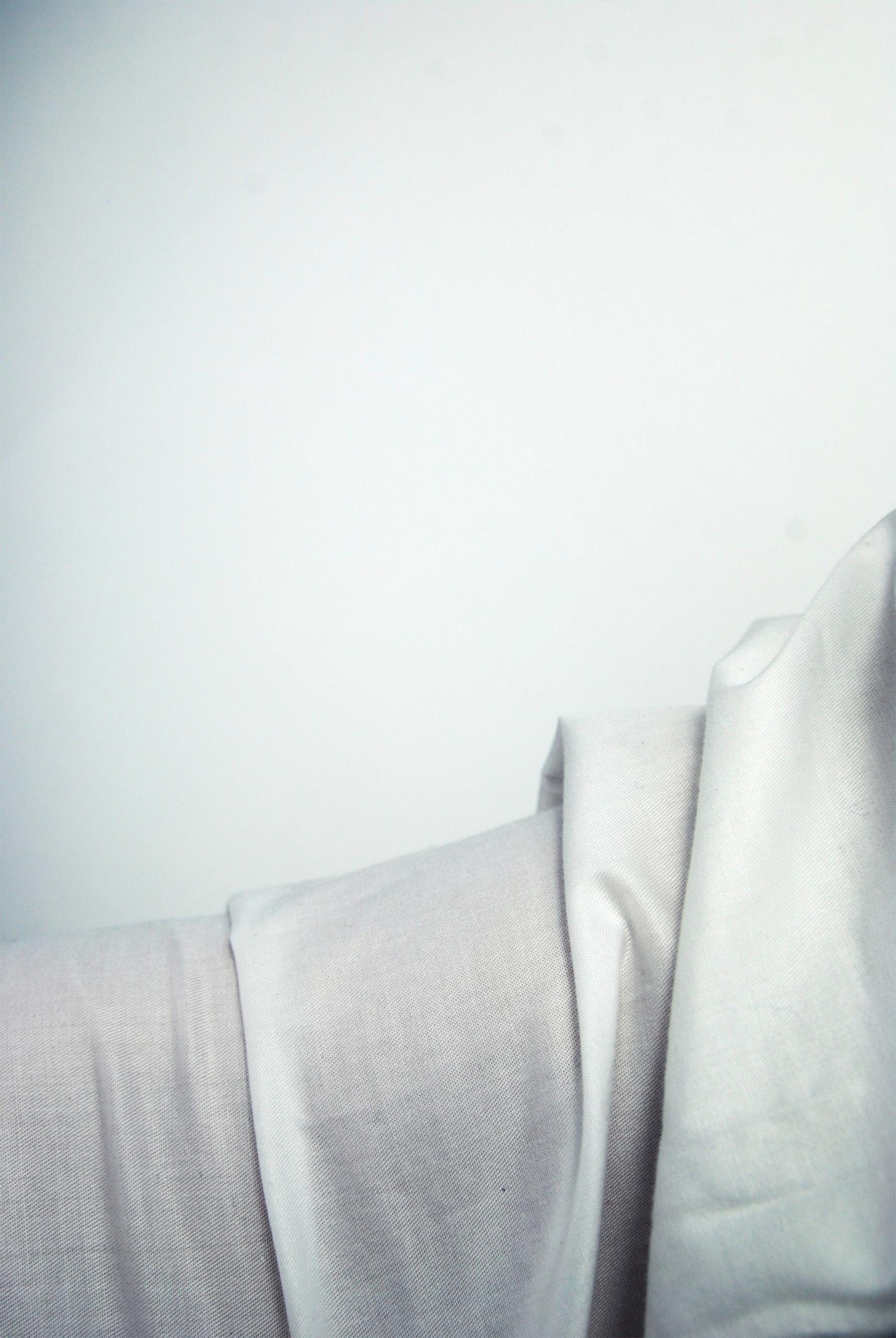 Zdjęcie przedstawia fragment białej tkaniny na białym tle.