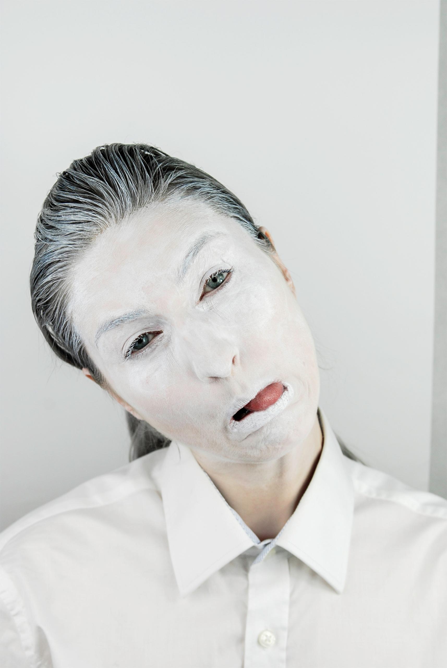 Zdjęcie przedstawia człowieka pomalowanego białą farbą, który przekrzywia głowę i usta.