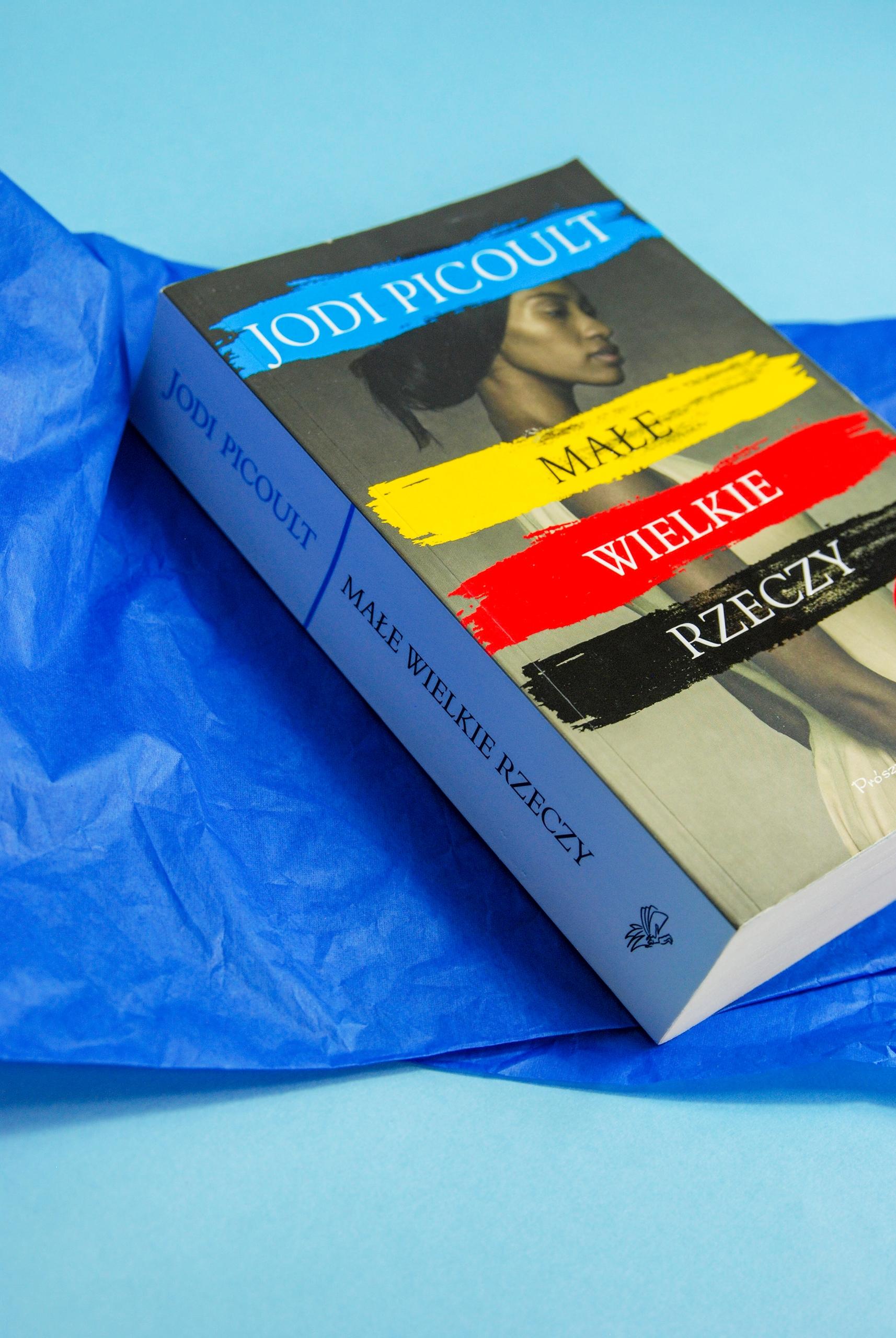 Zdjęcie przedstawia książkę leżącą na niebieskim papierze.