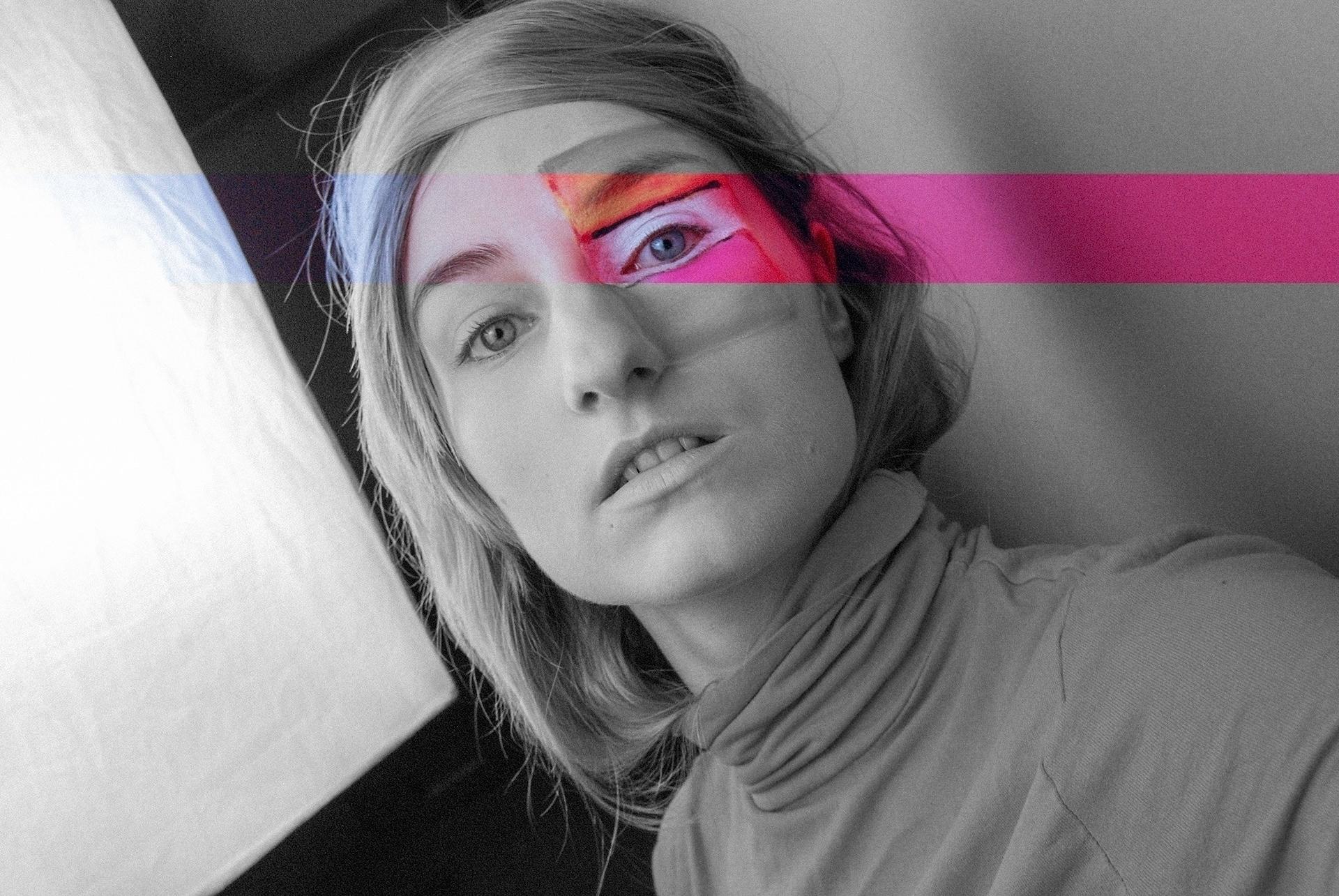 Zdjęcie przedstawia czarno-biały portret młodej kobiety. Na fragmencie jej twarzy widzimy 'prześwit' kolorów.