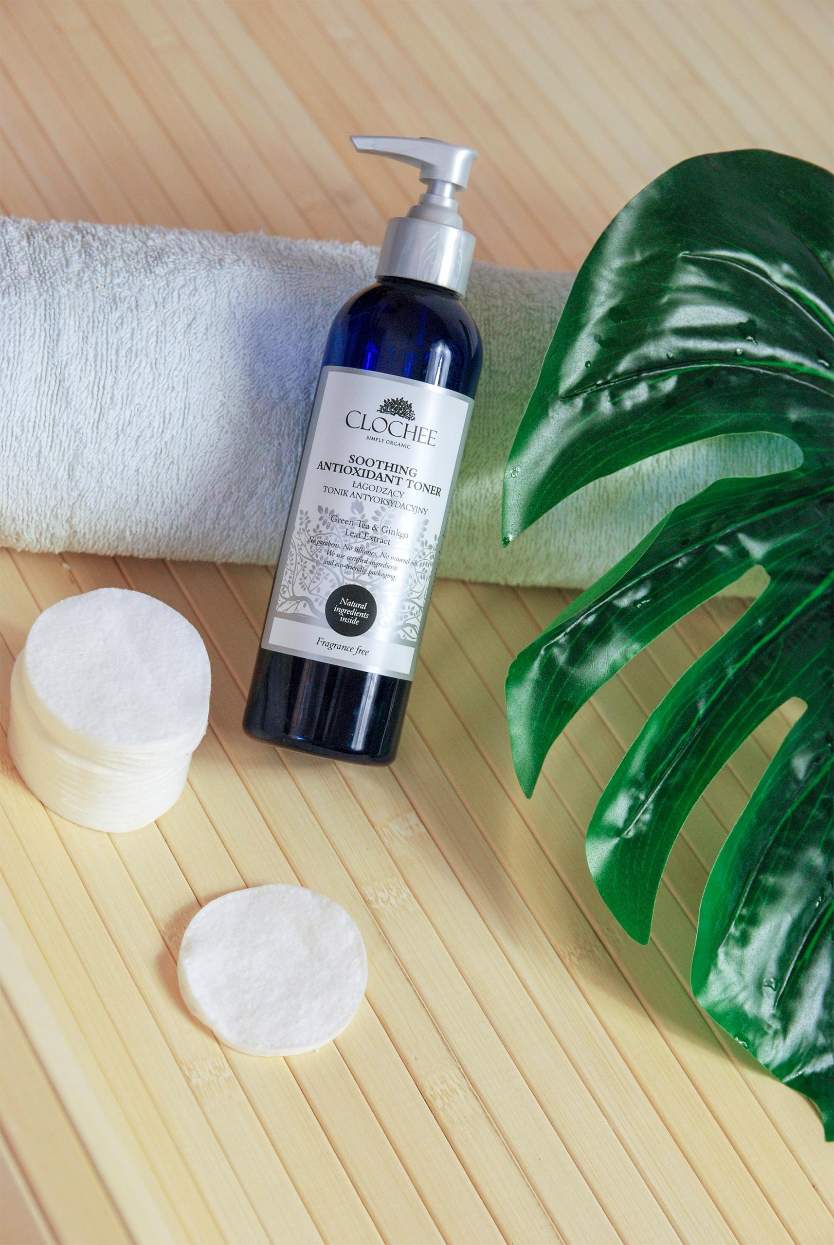 Zdjęcie przedstawia kosmetyk w otoczeniu wacików kosmetycznych, zielonej rośliny, ręcznika. Całość na drewnianym podłożu.