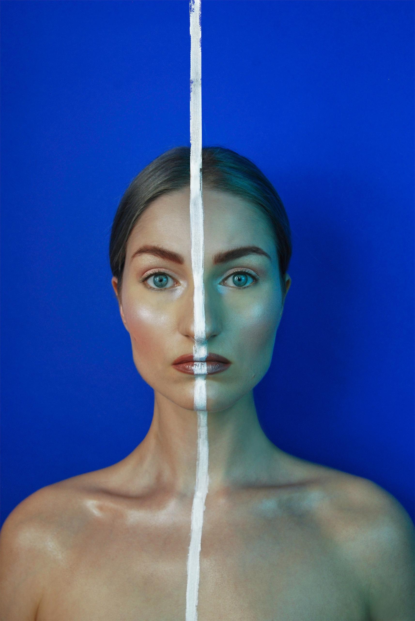 Fotografia przedstawia portret młodej kobiety, która patrzy wprost na nas, a przez jej twarz i ciało biegnie biała linia. Całość na niebieskim tle.