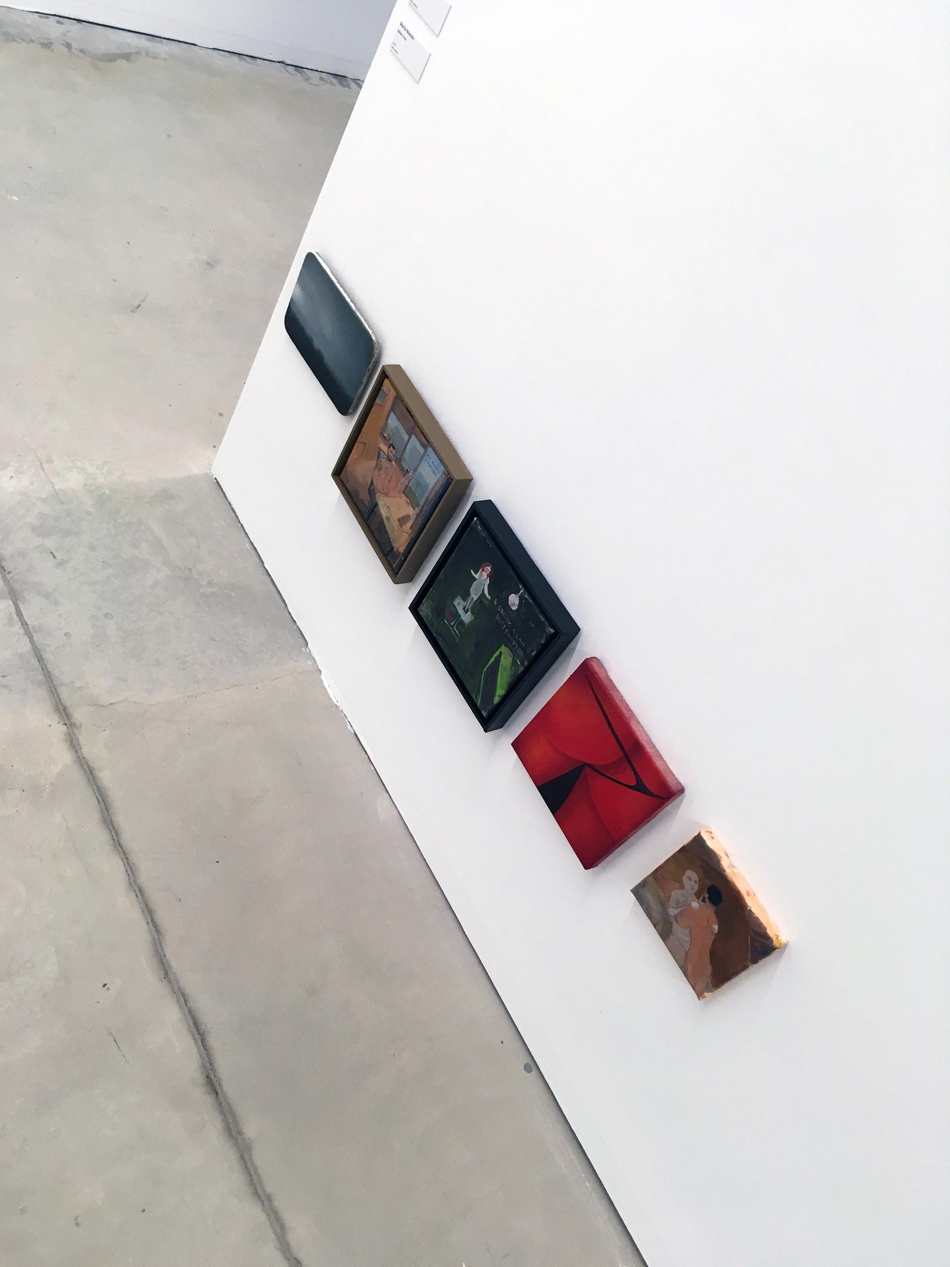 Zdjęcie przedstawia niewielkich formatów obrazki zawieszone na białej ścianie bardzo blisko podłogi.