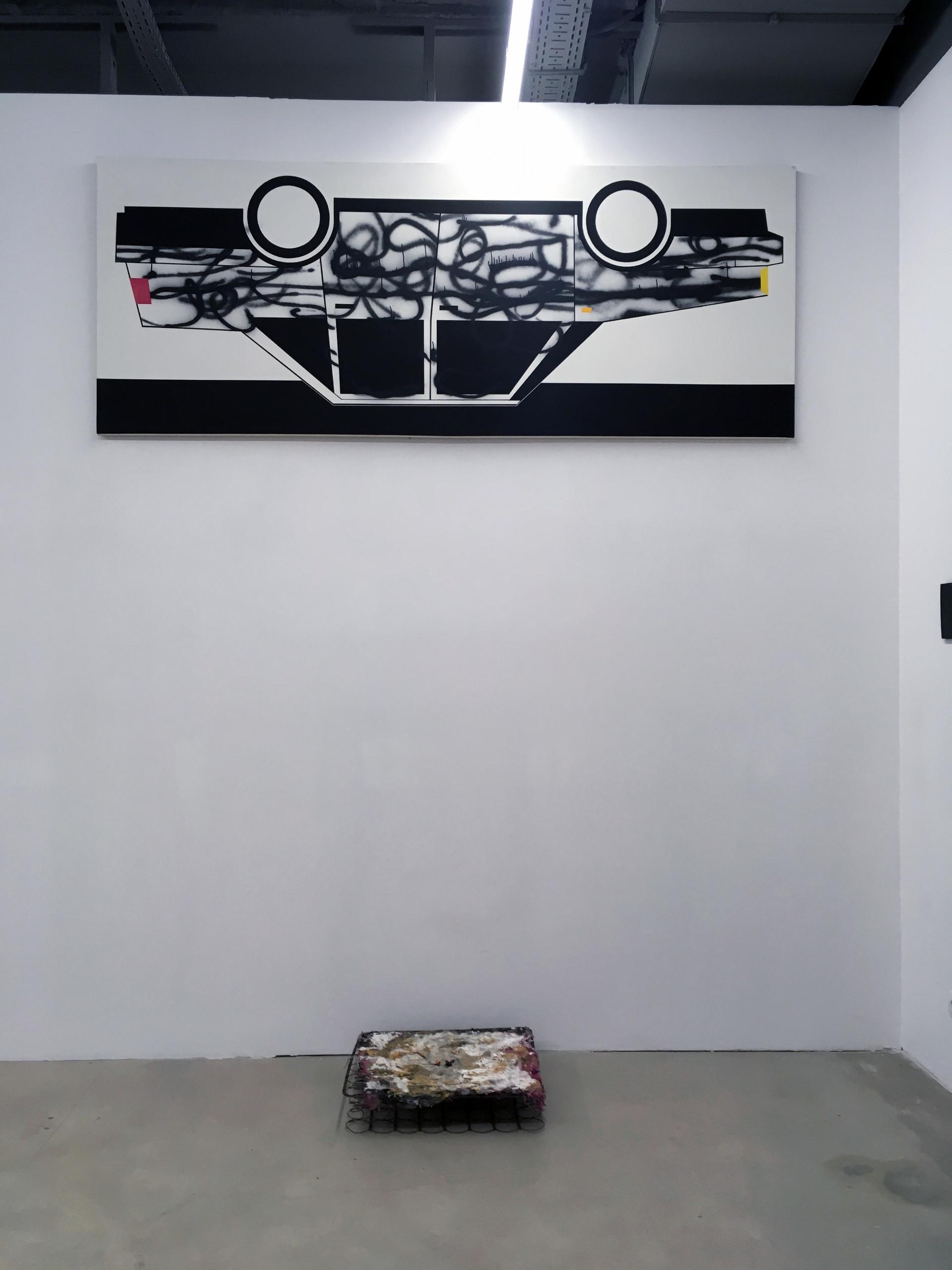 Zdjęcie przedstawia wnętrze galerii sztuki z pracami artystów.