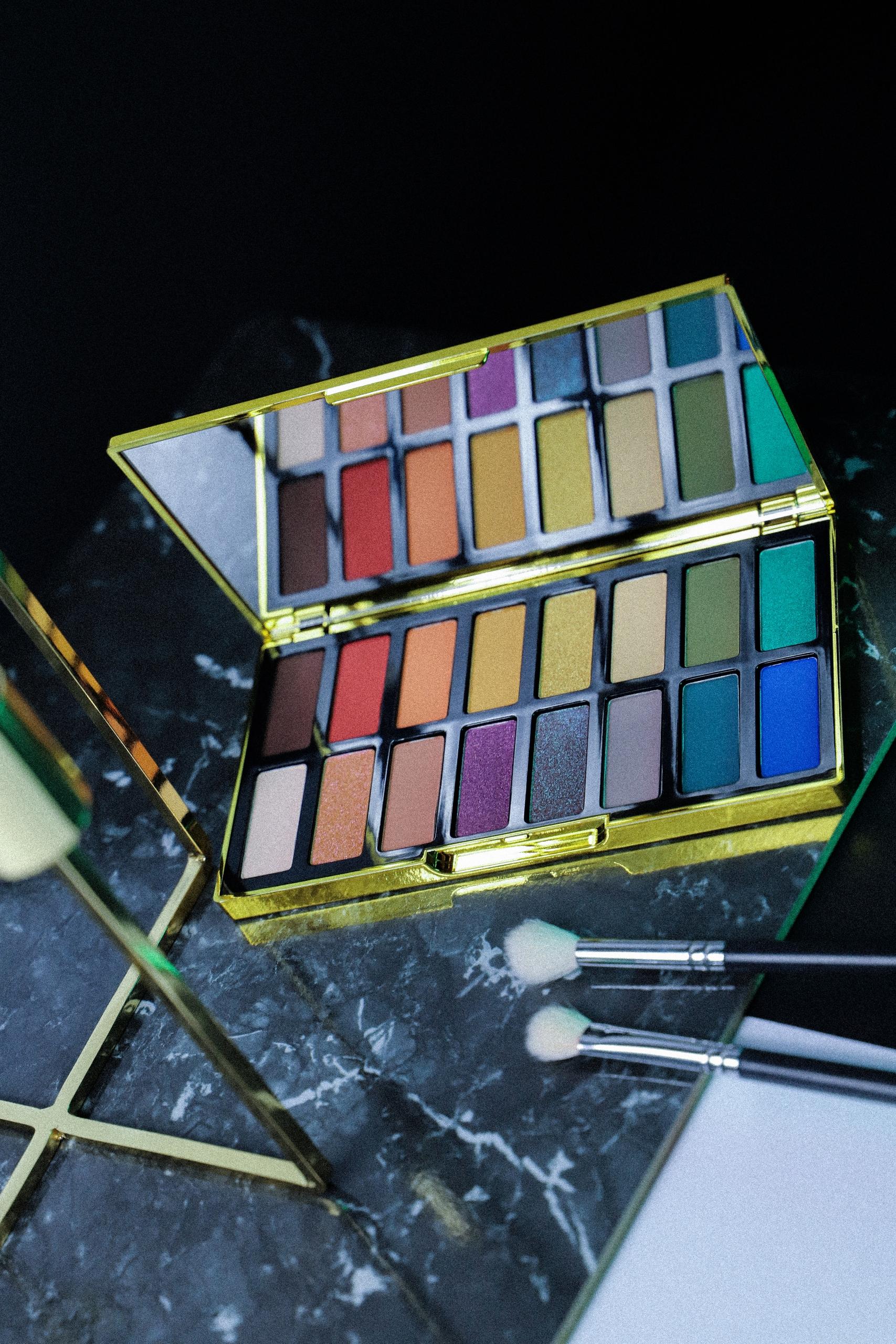 Zdjęcie przedstawia paletę cieni do malowania oczu, całość zdjęcia w ciemnej kolorystyce.