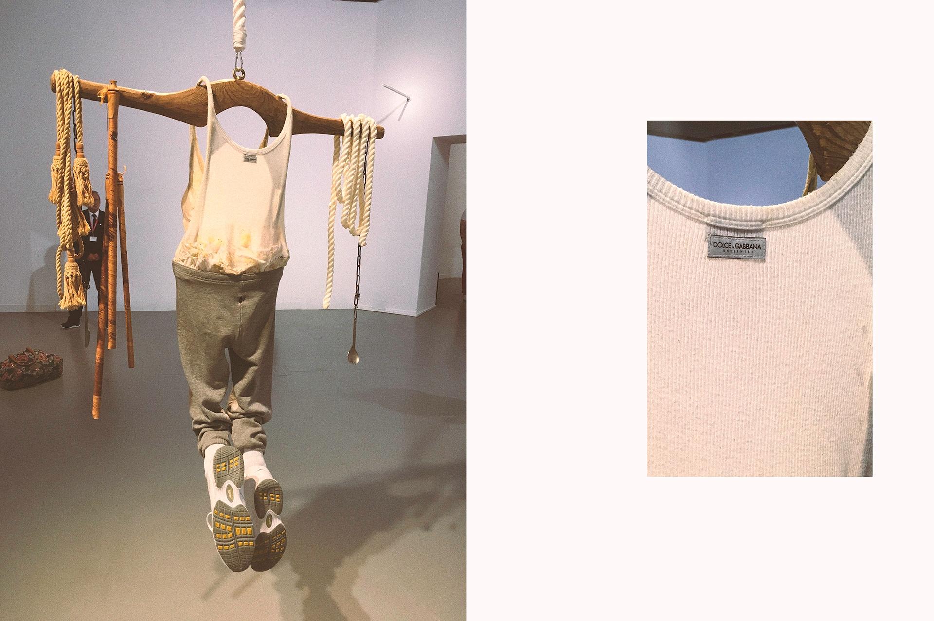 Obraz przedstawia dwa zdjęcia rzeźby zawieszonej w przestrzeni muzeum. Na jednym ze zdjęć widzimy zbliżenie na białą koszulkę.