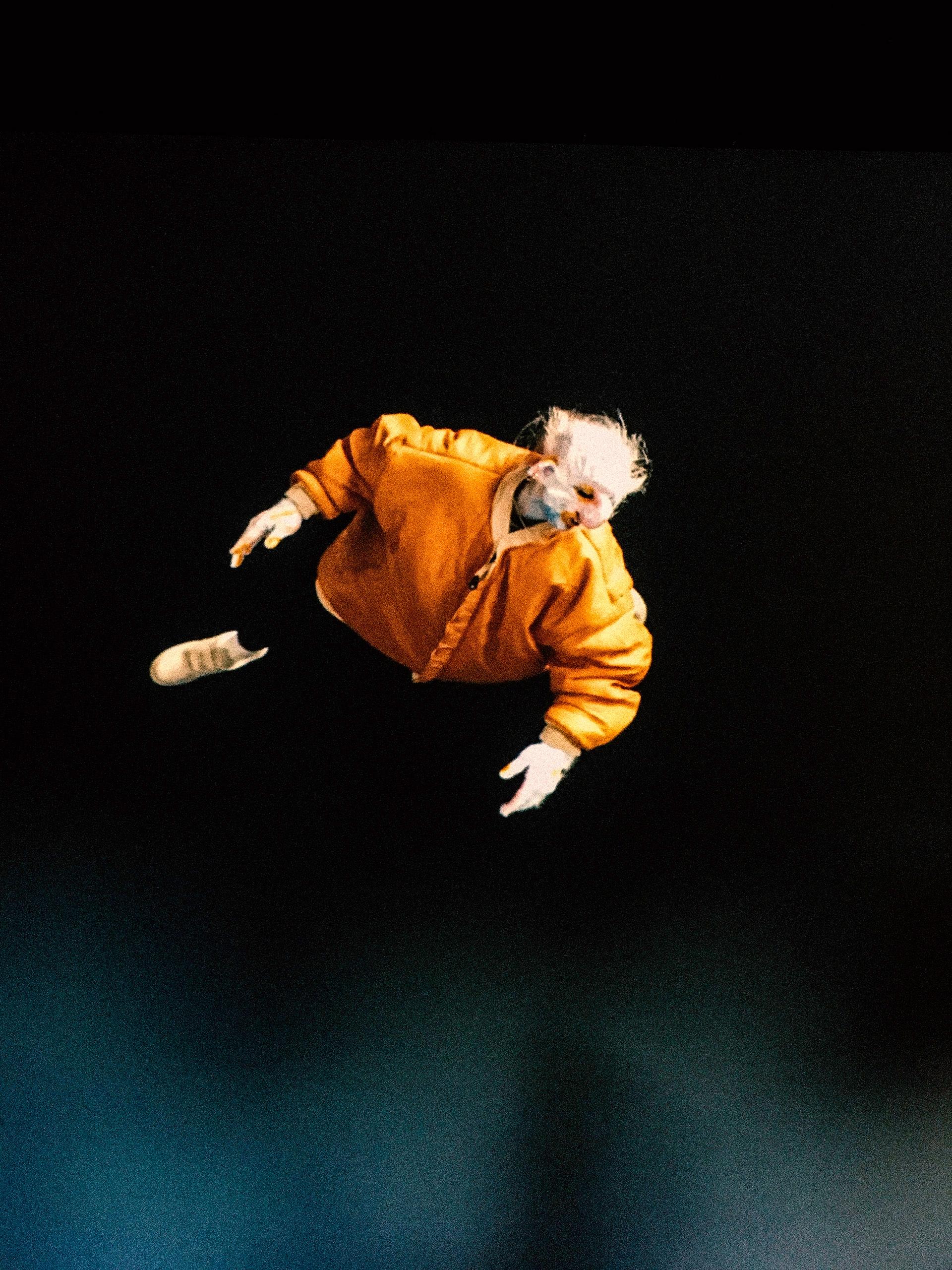 Zdjęcie przedstawia postać w pomarańczowym ubraniu na czarnym tle.