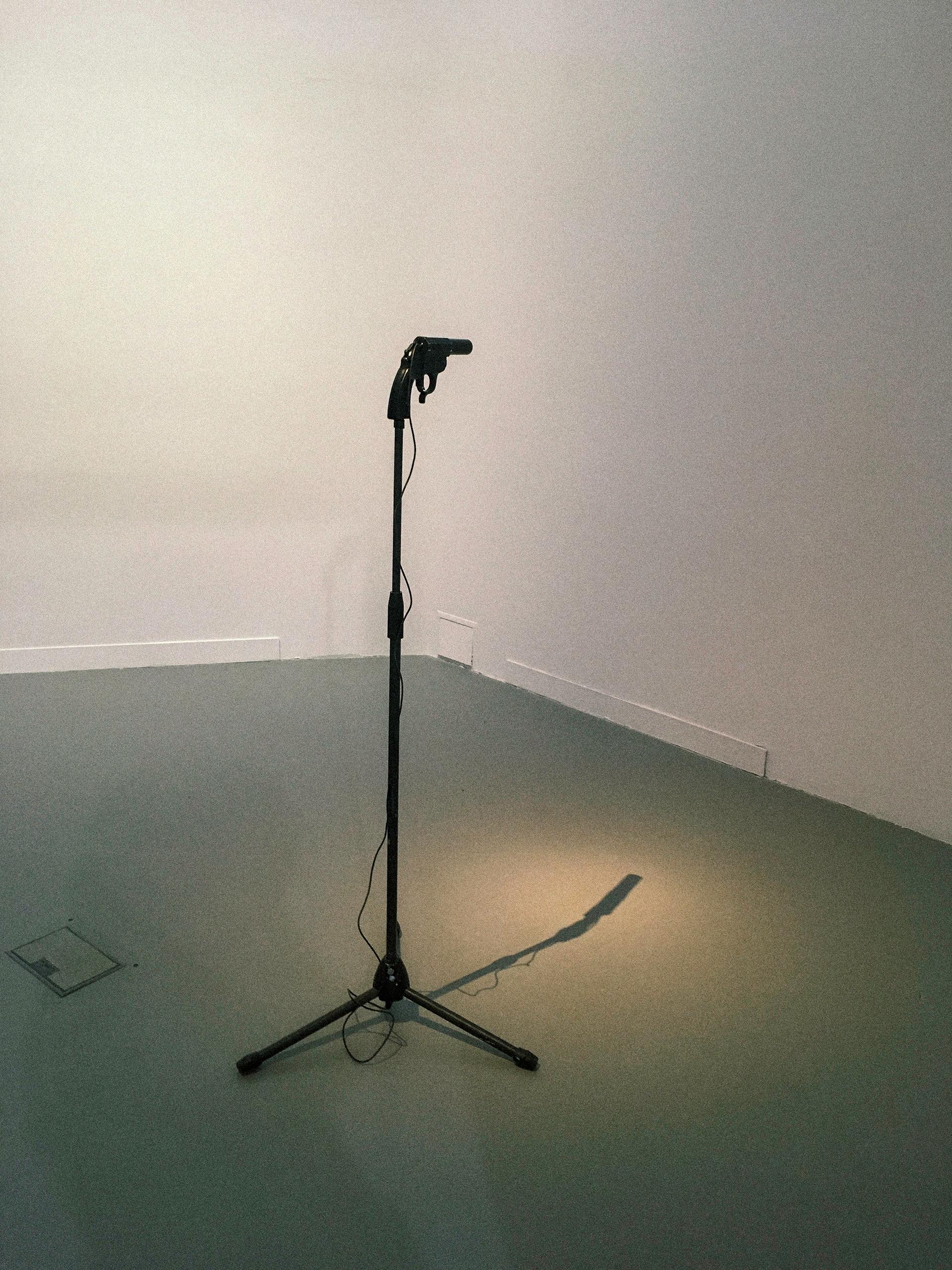 Zdjęcie przedstawia obiekt przypominający czarny mikrofon znajdujący się w białym pomieszczeniu.