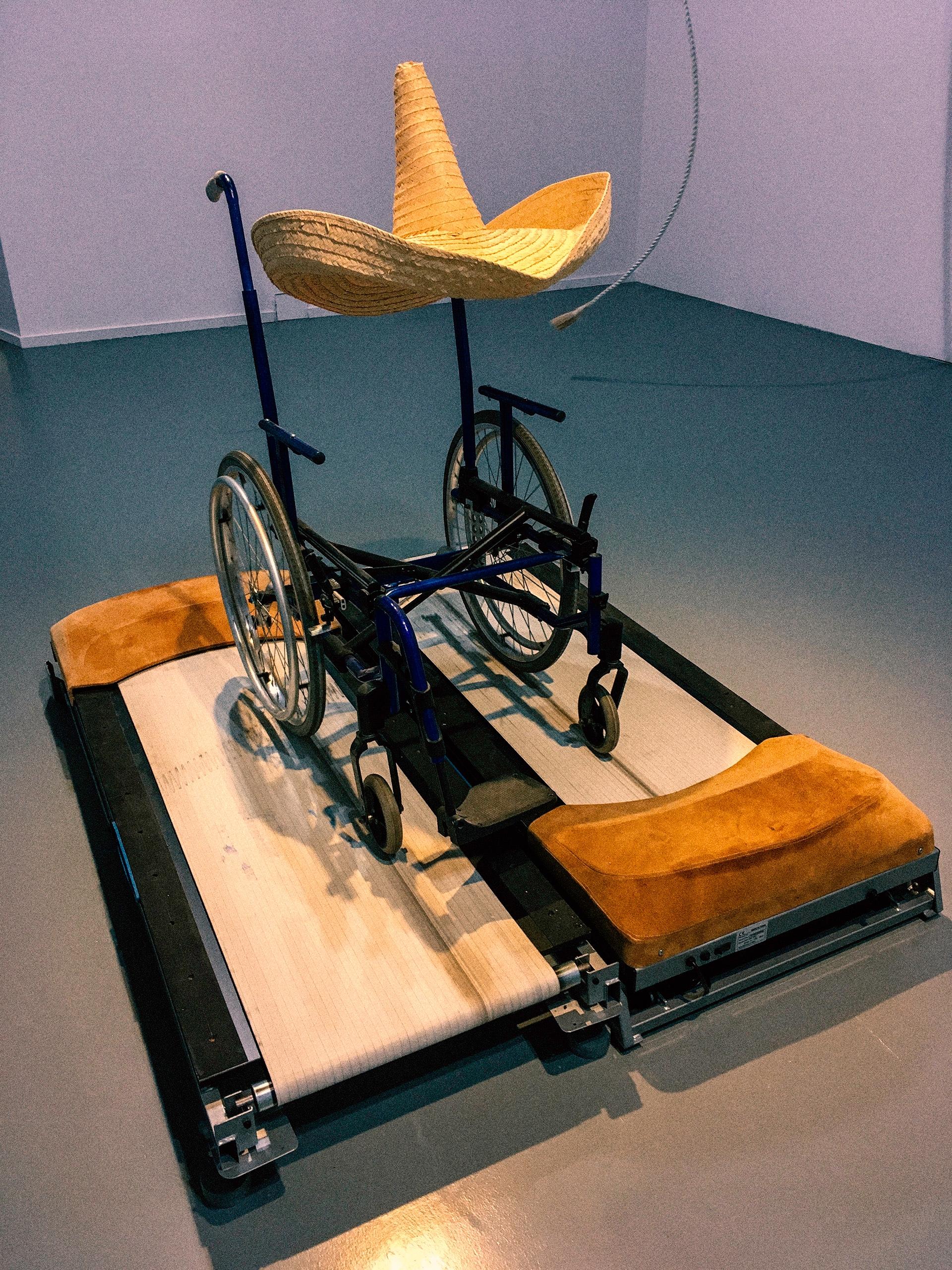 Zdjęcie przedstawia wózek inwalidzki z meksykańskim kapeluszem zawieszonym na jego uchwycie.