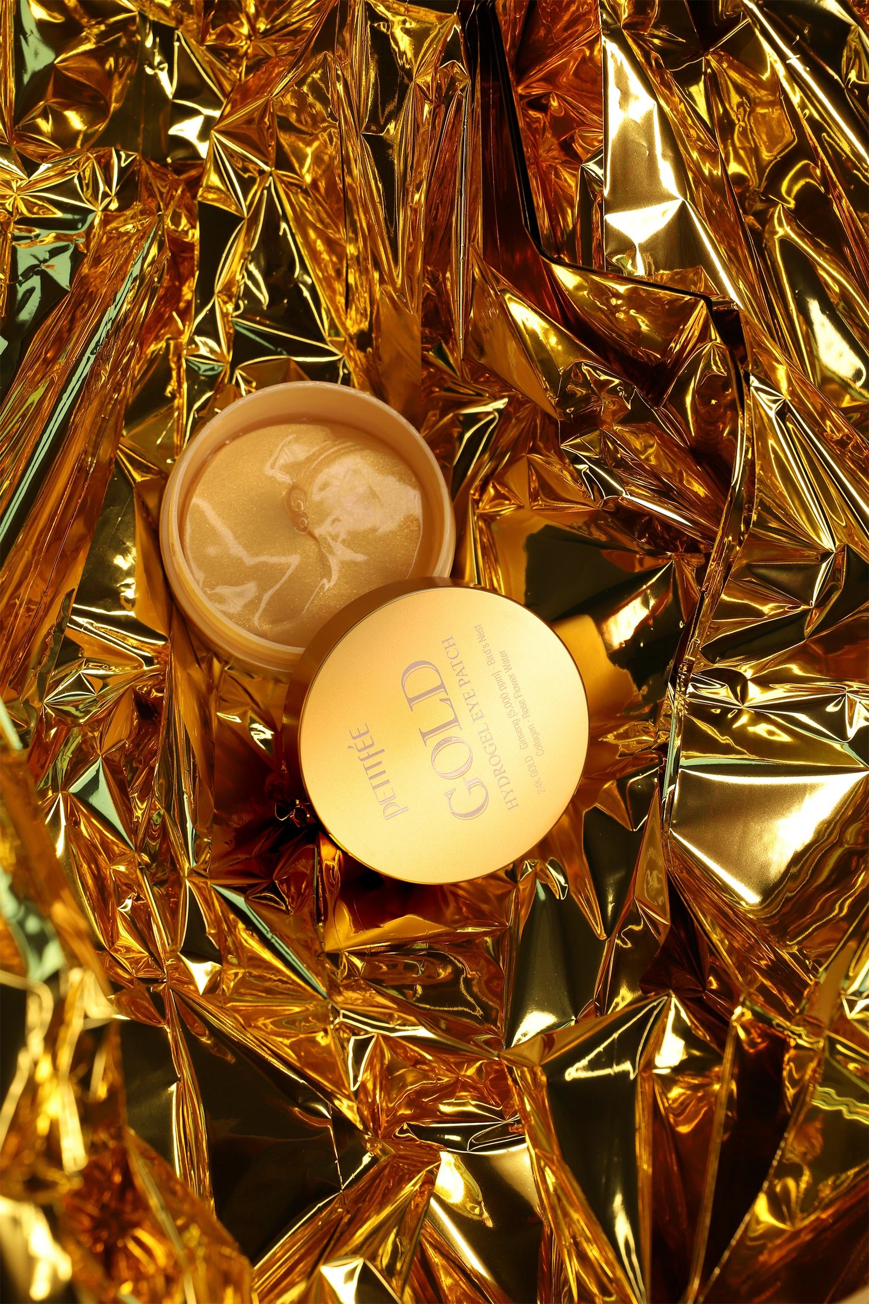 Zdjęcie przedstawia okrągłe złote pudełko leżące na złotej folii.