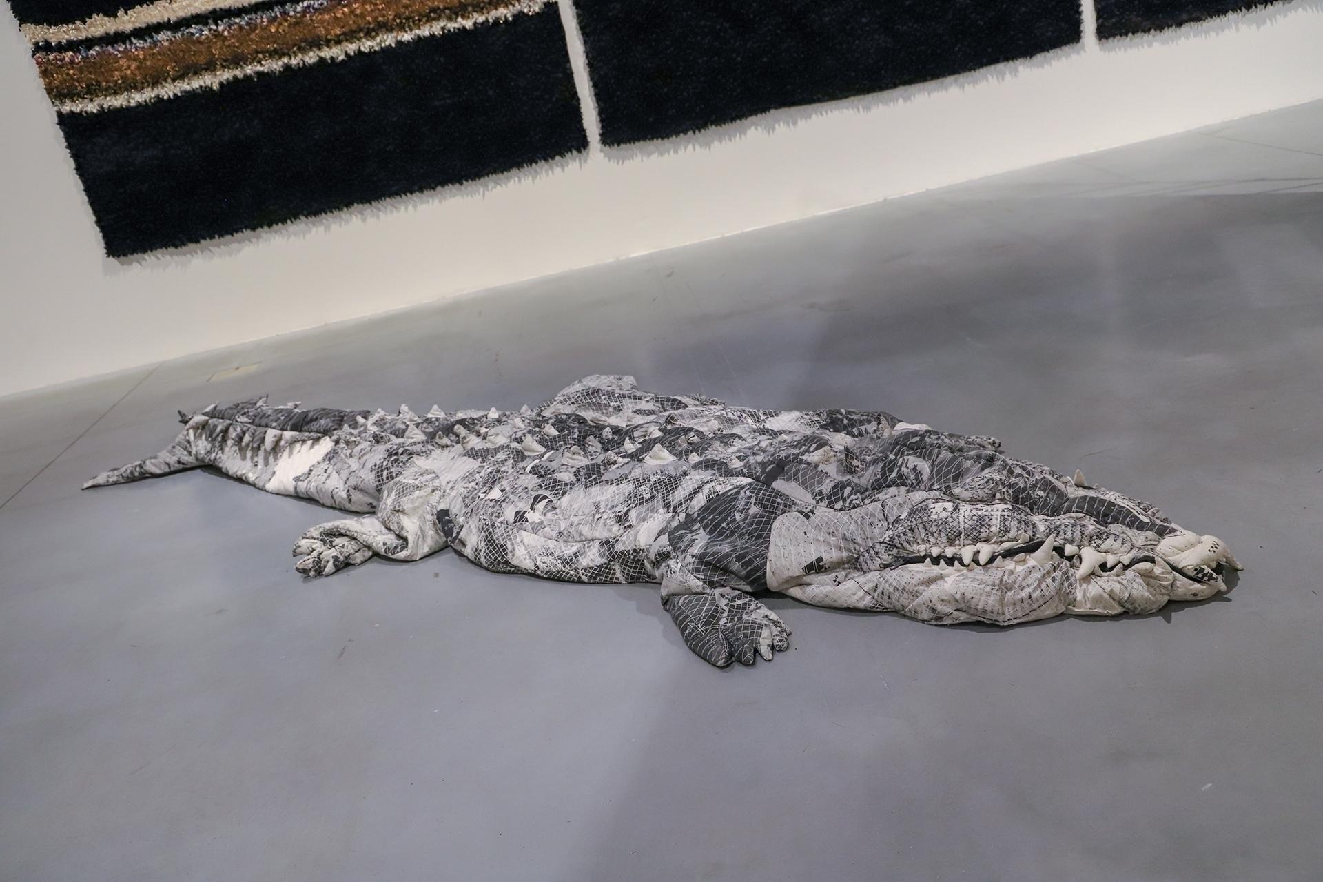 Zdjęcie przedstawia figurę szarego krokodyla leżącą na podłodze.