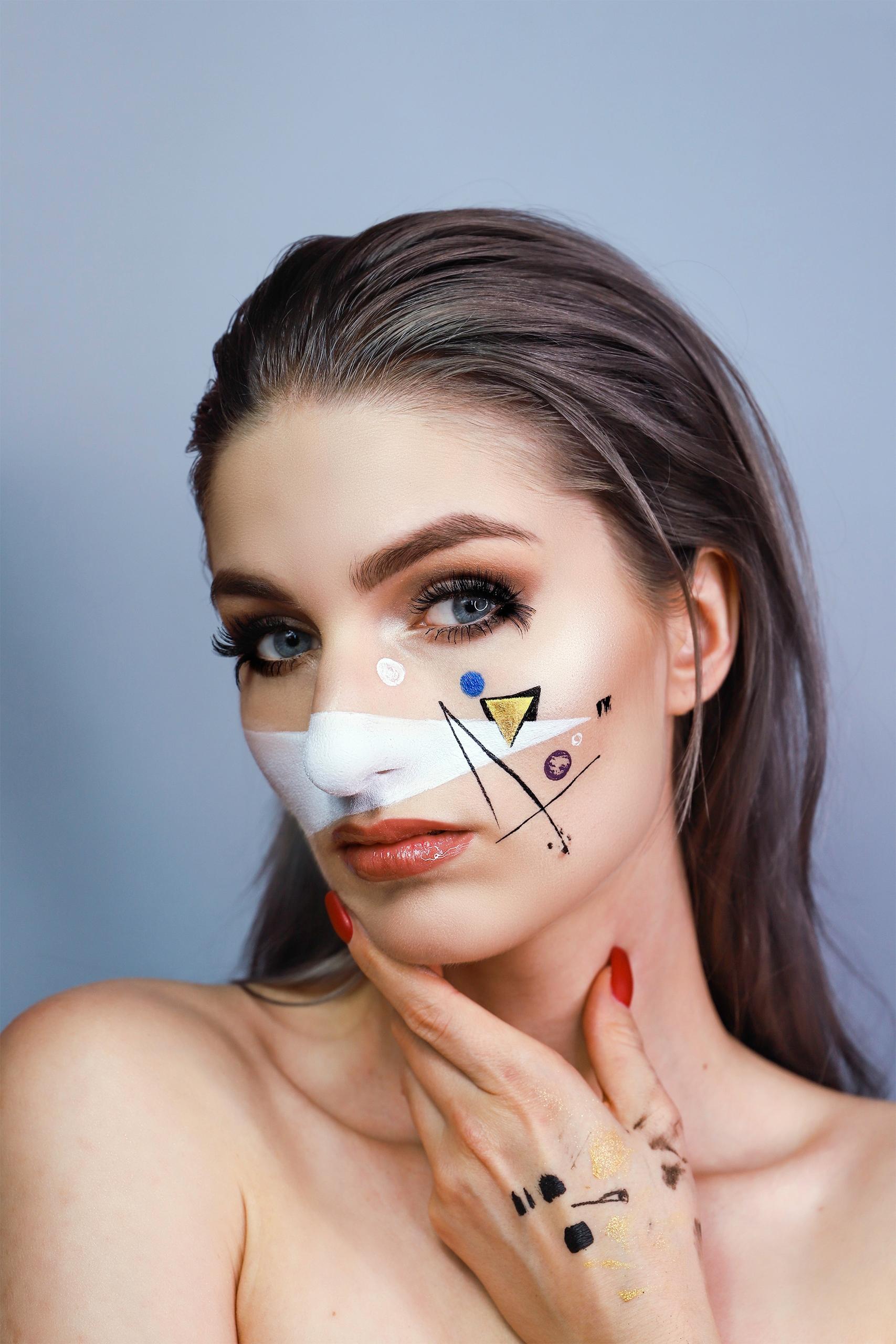 Zdjęcie przedstawia portret kobiety na szarym tle. Kobieta ma lekko przechyloną głowę i trzyma twarz ręką. Na jej lewym policzku widzimy graficzny makijaż.