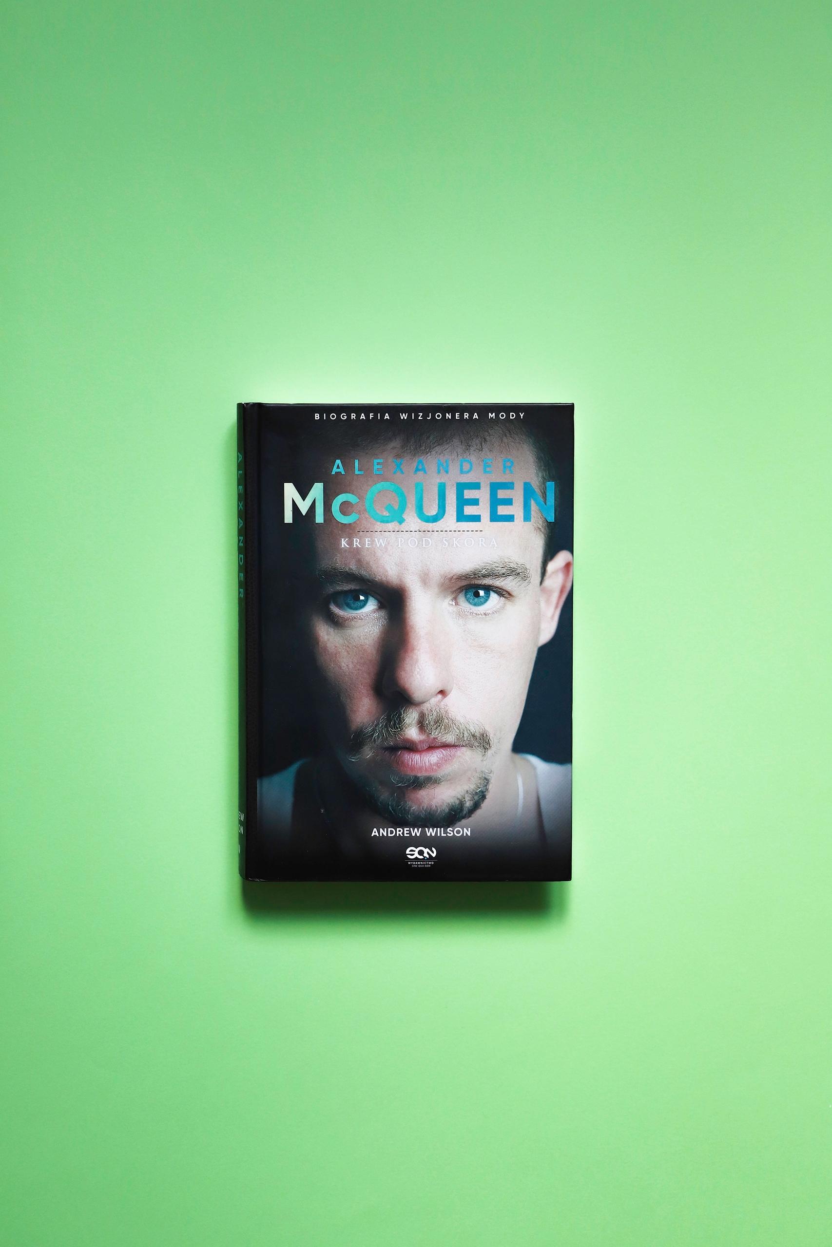 Zdjęcie przedstawia książkę leżącą na zielonym podłożu. Na jej okładce widzimy portret mężczyzny.