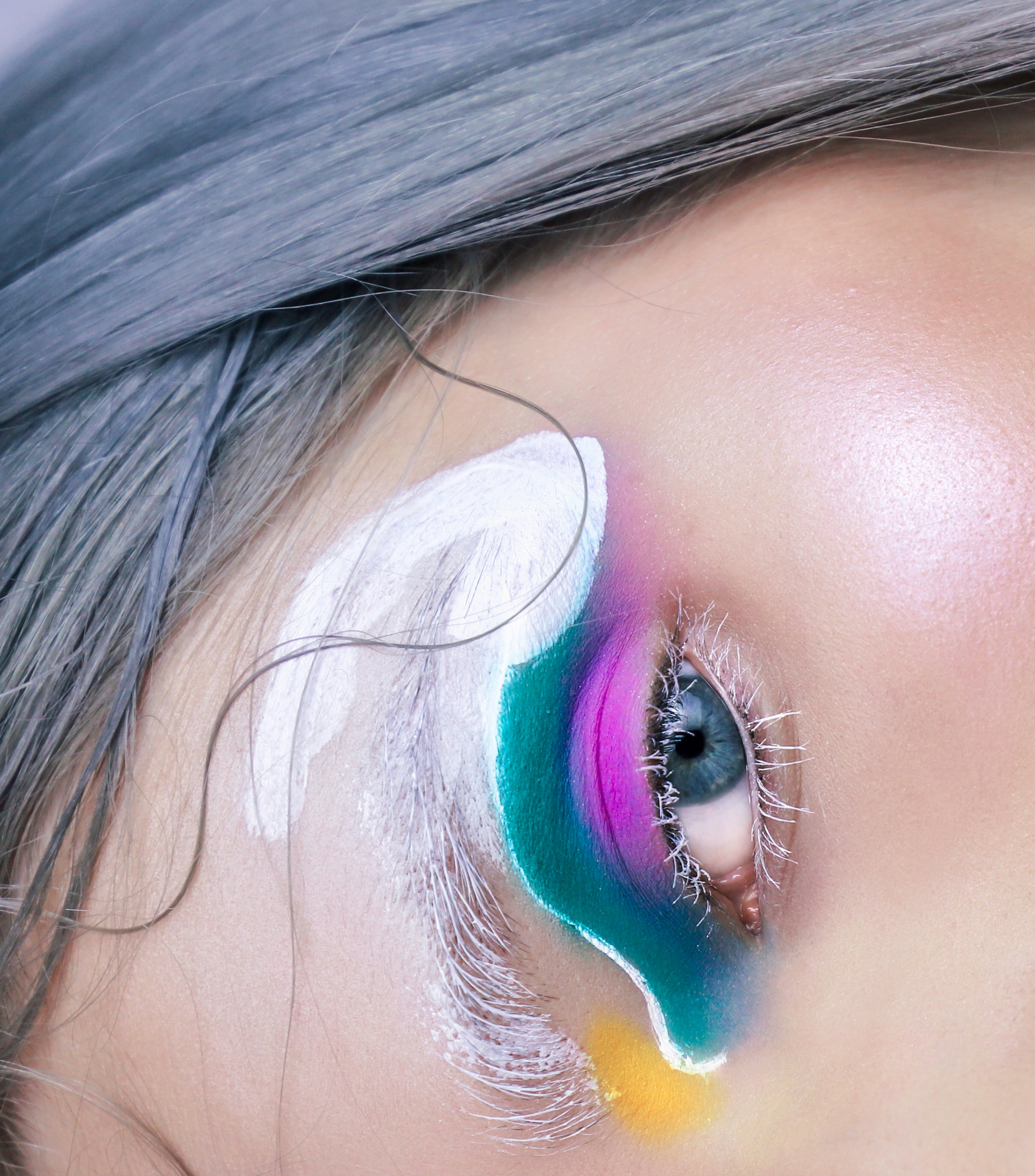 Zdjęcie przedstawia zbliżenie na oko w artystycznym makijażu.