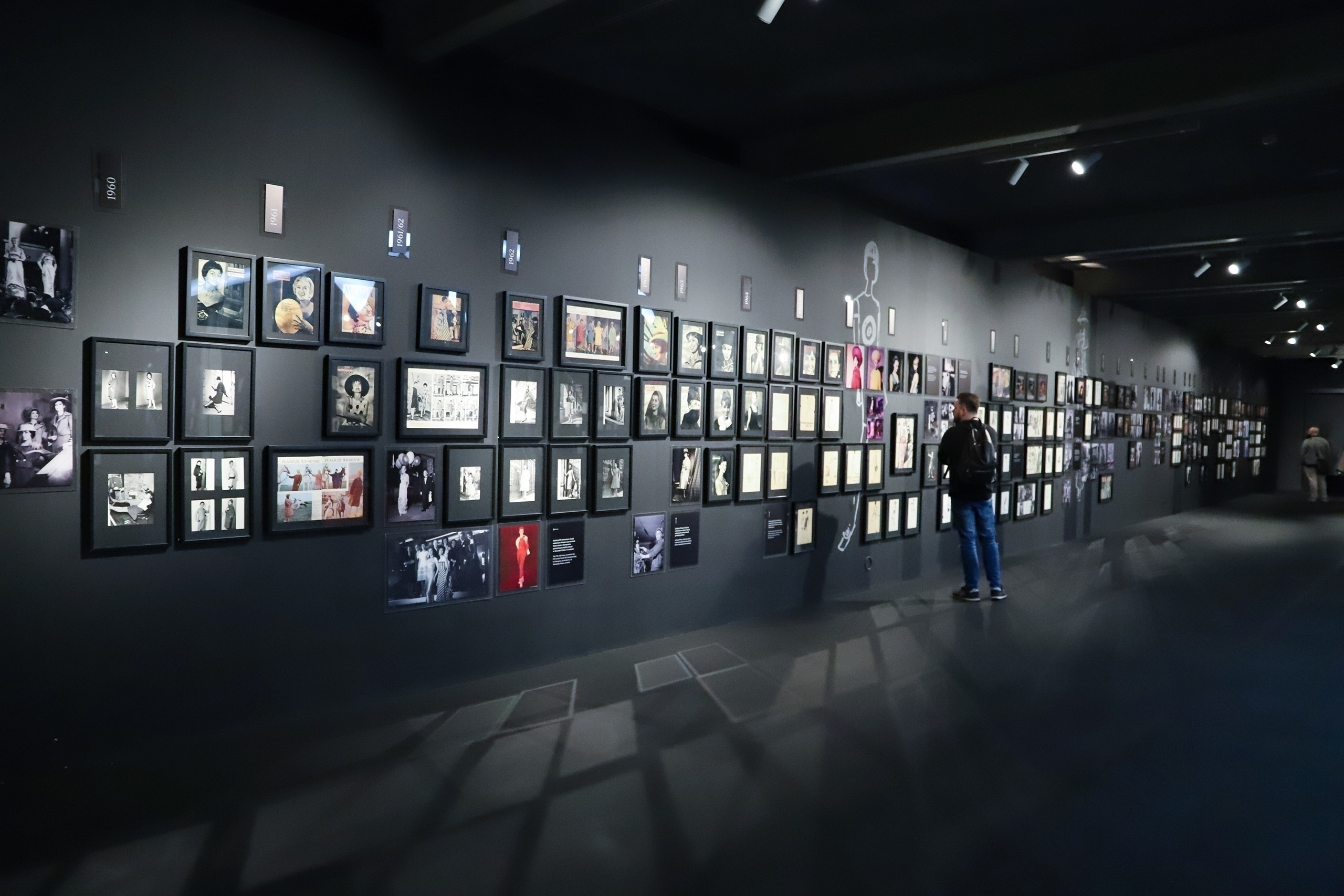 Zdjęcie przedstawia pomieszczenie z czarnymi ścianami, na których wiszą małe fotografie oprawione w ramki.