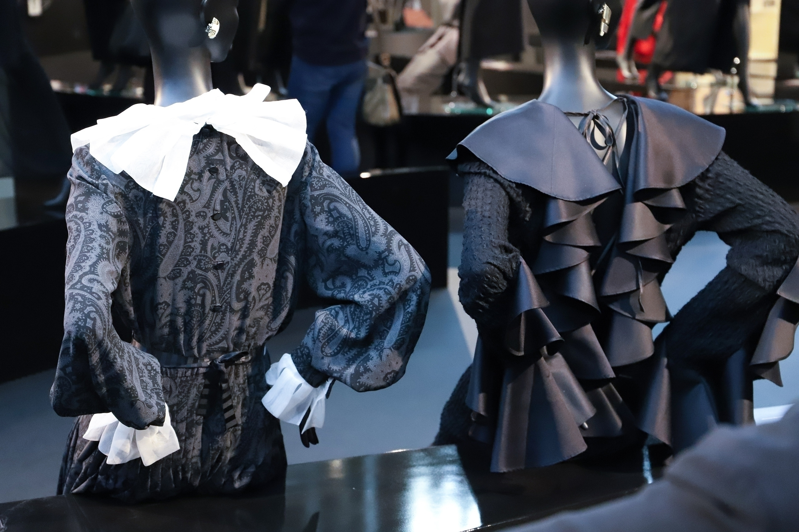 Zdjęcie przedstawia plecy dwóch siedzących manekinów ubranych w ciemne ubrania.