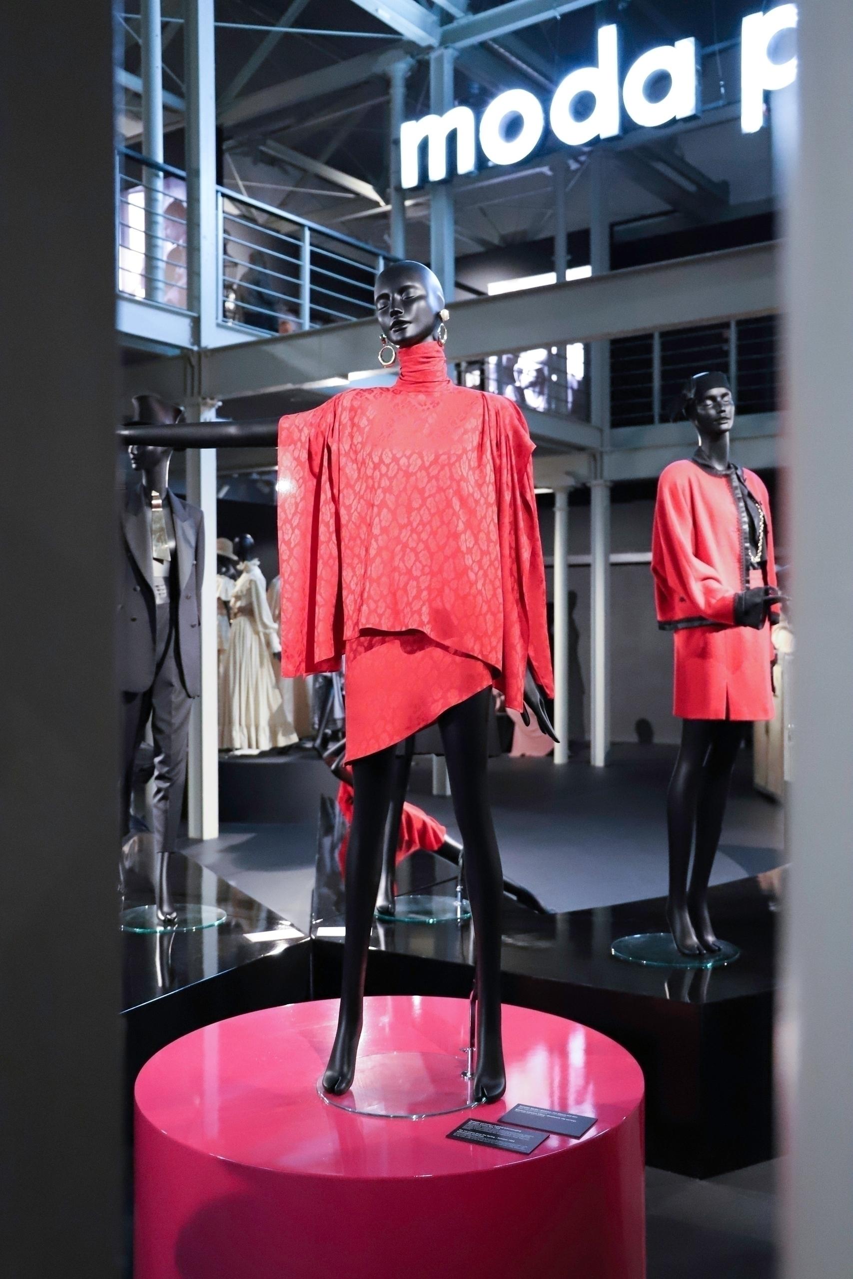 Zdjęcie przedstawia czarnego manekina ubranego w czerwoną sukienkę stojącego na podeście.