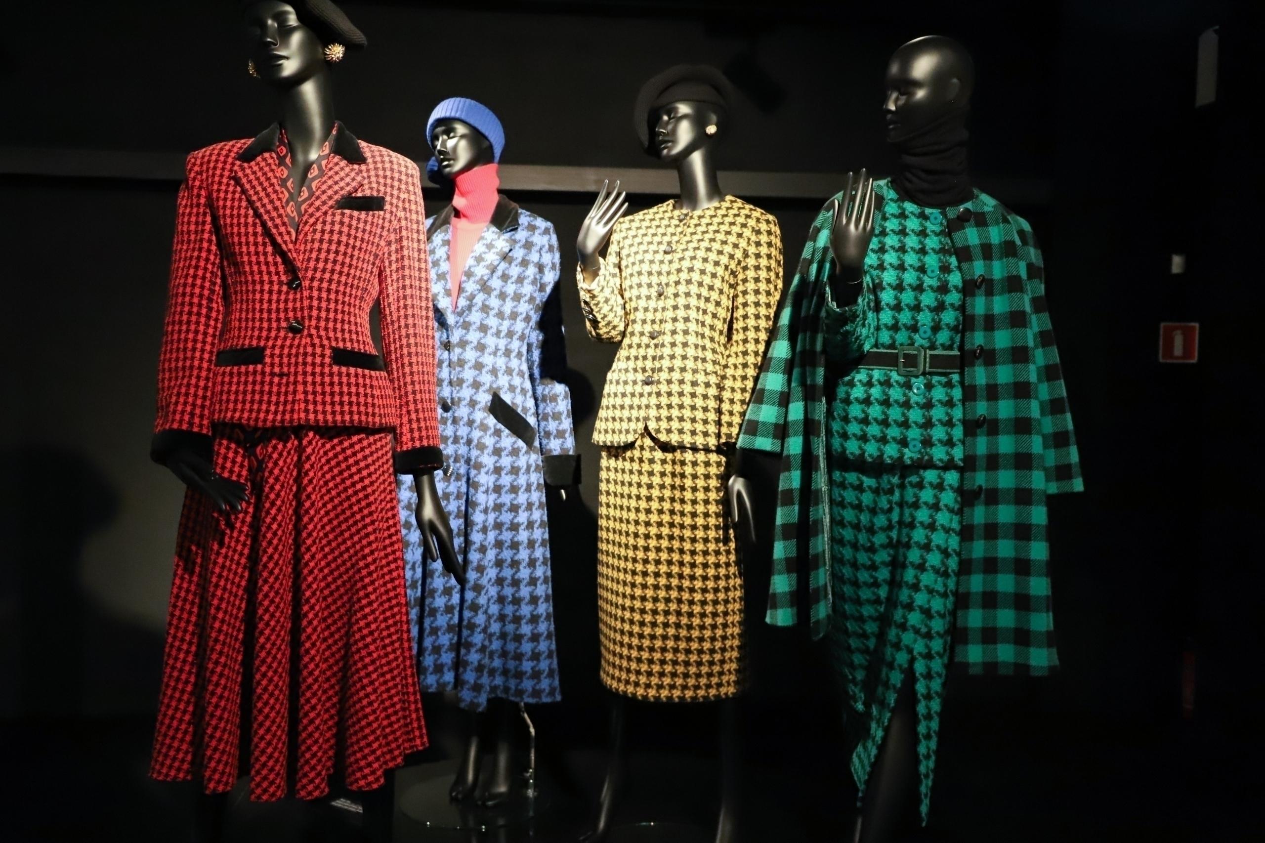 Zdjęcie przedstawia cztery manekiny ubrane w czerwony, niebieski, żółty i zielony kostium.
