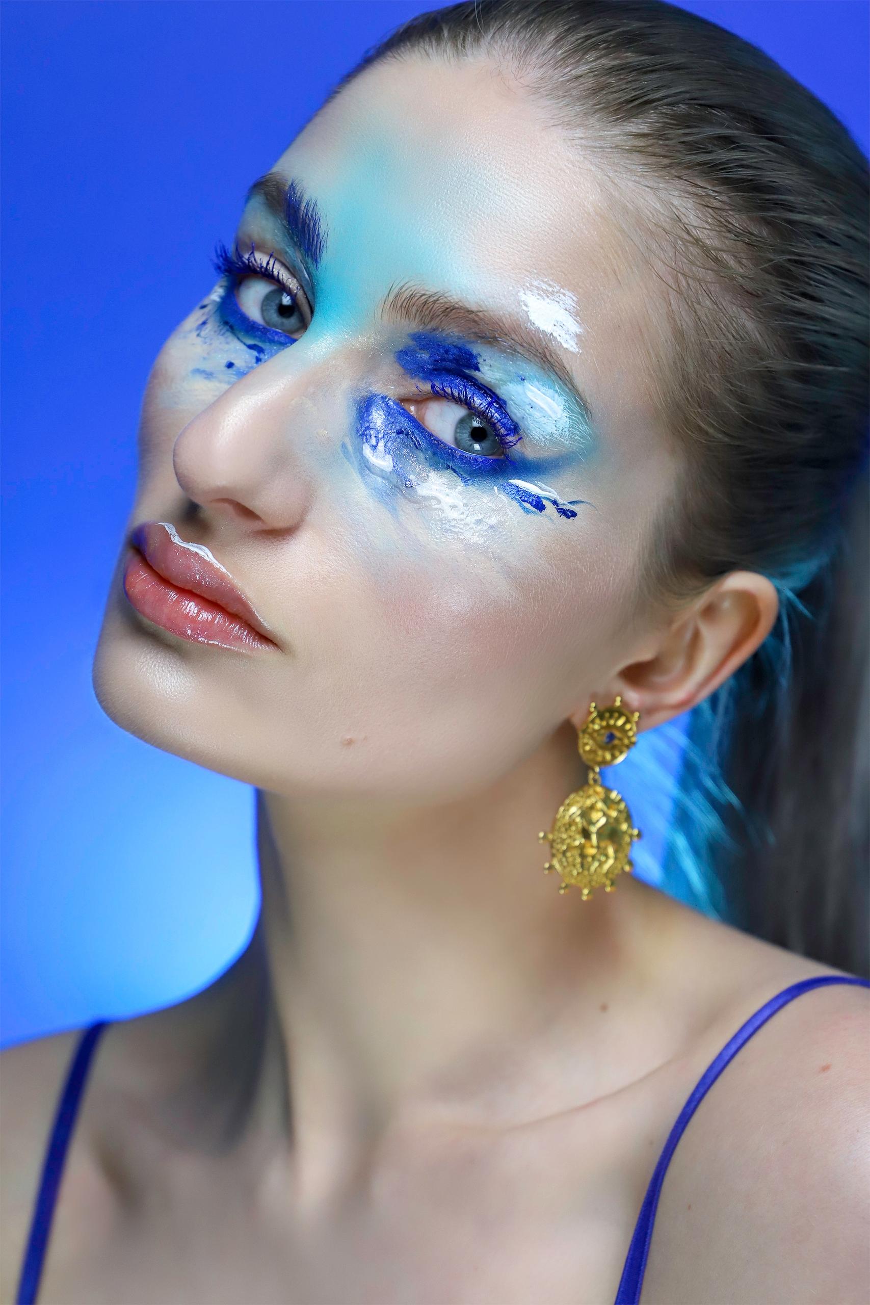 Zdjęcie przedstawia portret kobiety z przekrzywioną głową. Kobieta ma na twarzy artystyczny makijaż w niebieskich odcieniach. Całość na niebieskim tle.