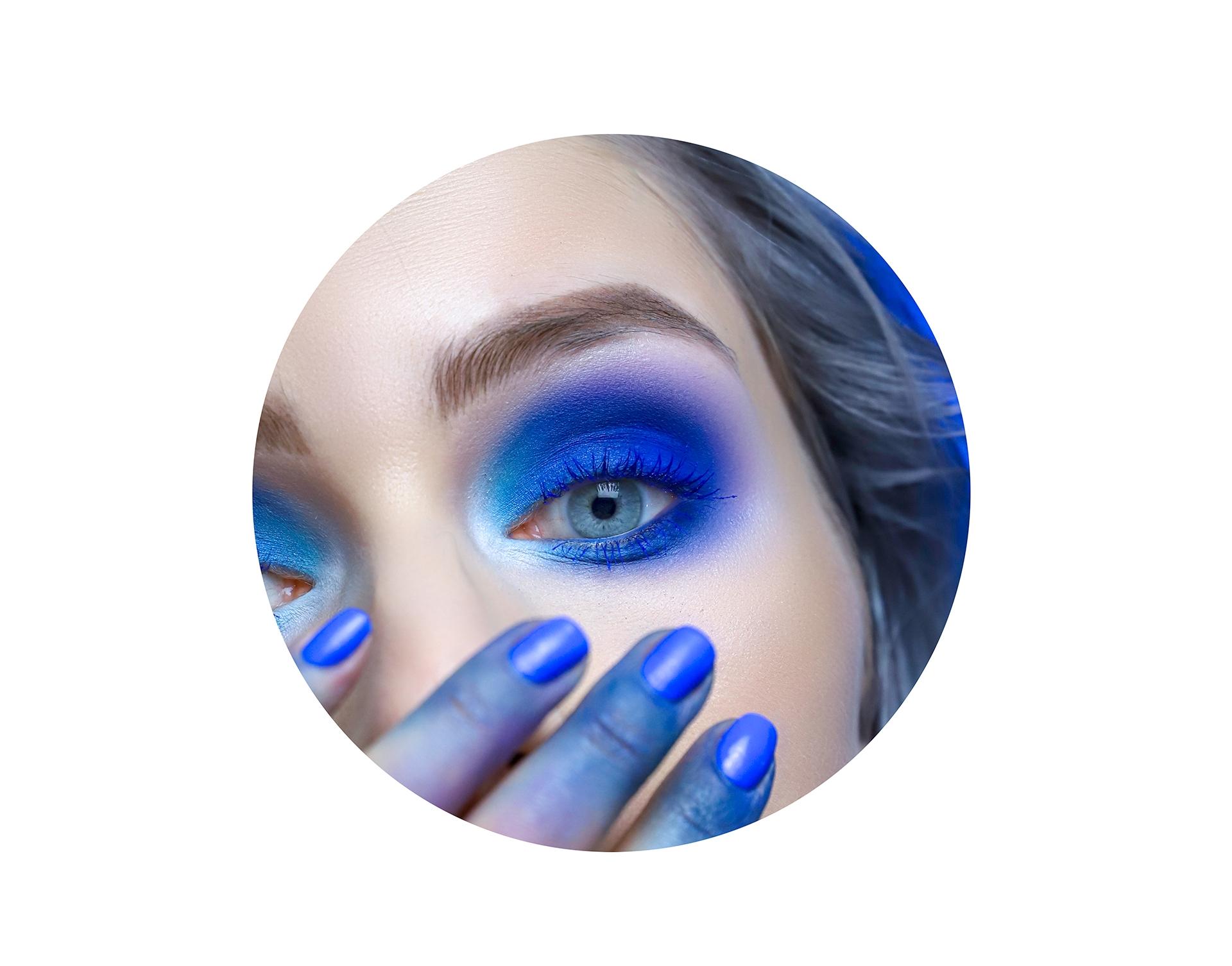 Zdjęcie przedstawia oko w niebieskim makijażu. Zdjęcie jest wpisane w kształt koła.