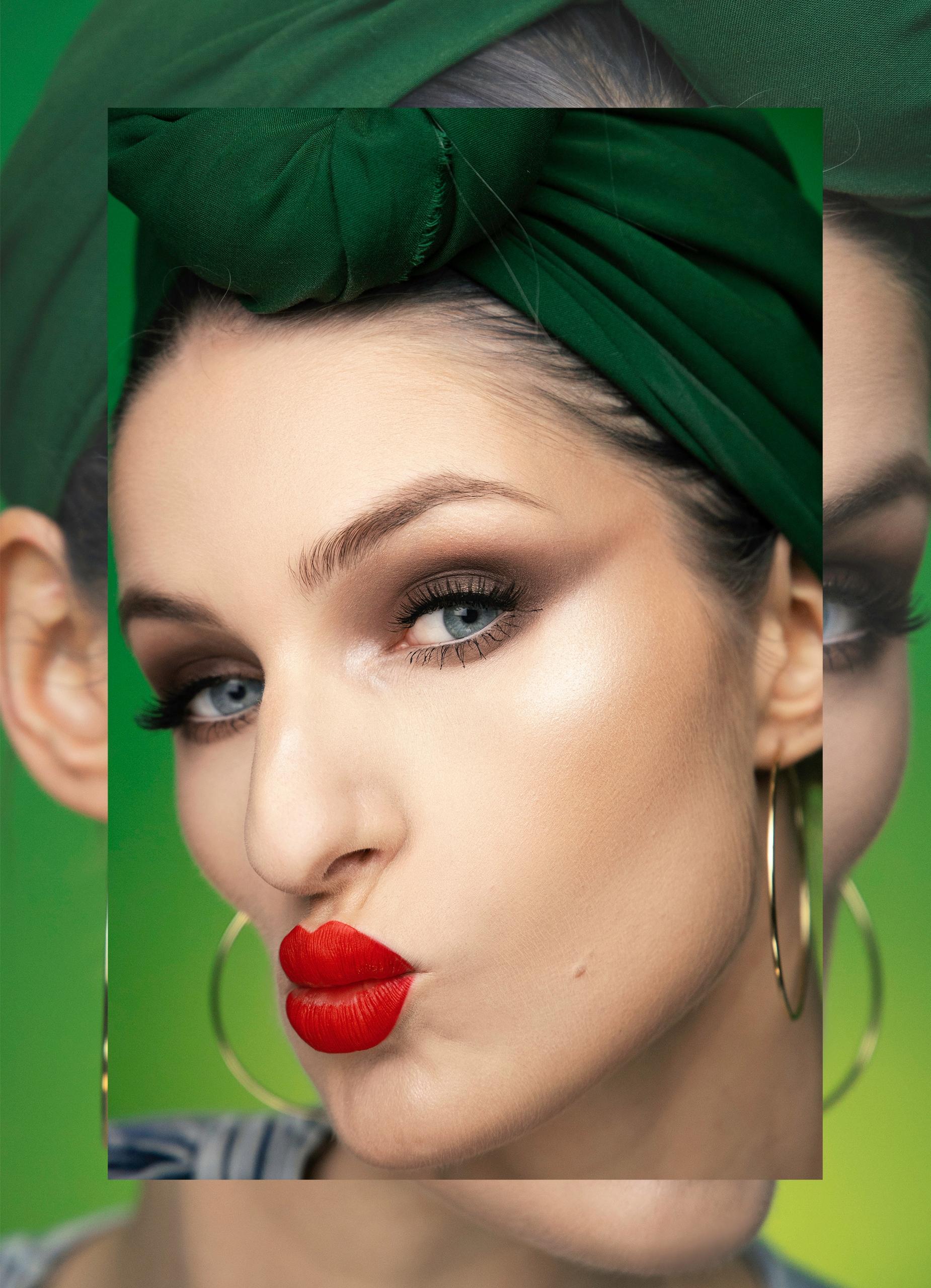 Obraz przestawia twarz kobiety z czerwonymi ustami. Kobieta ma na głowie zieloną chustkę, a usta układa w grymaśnej minie.