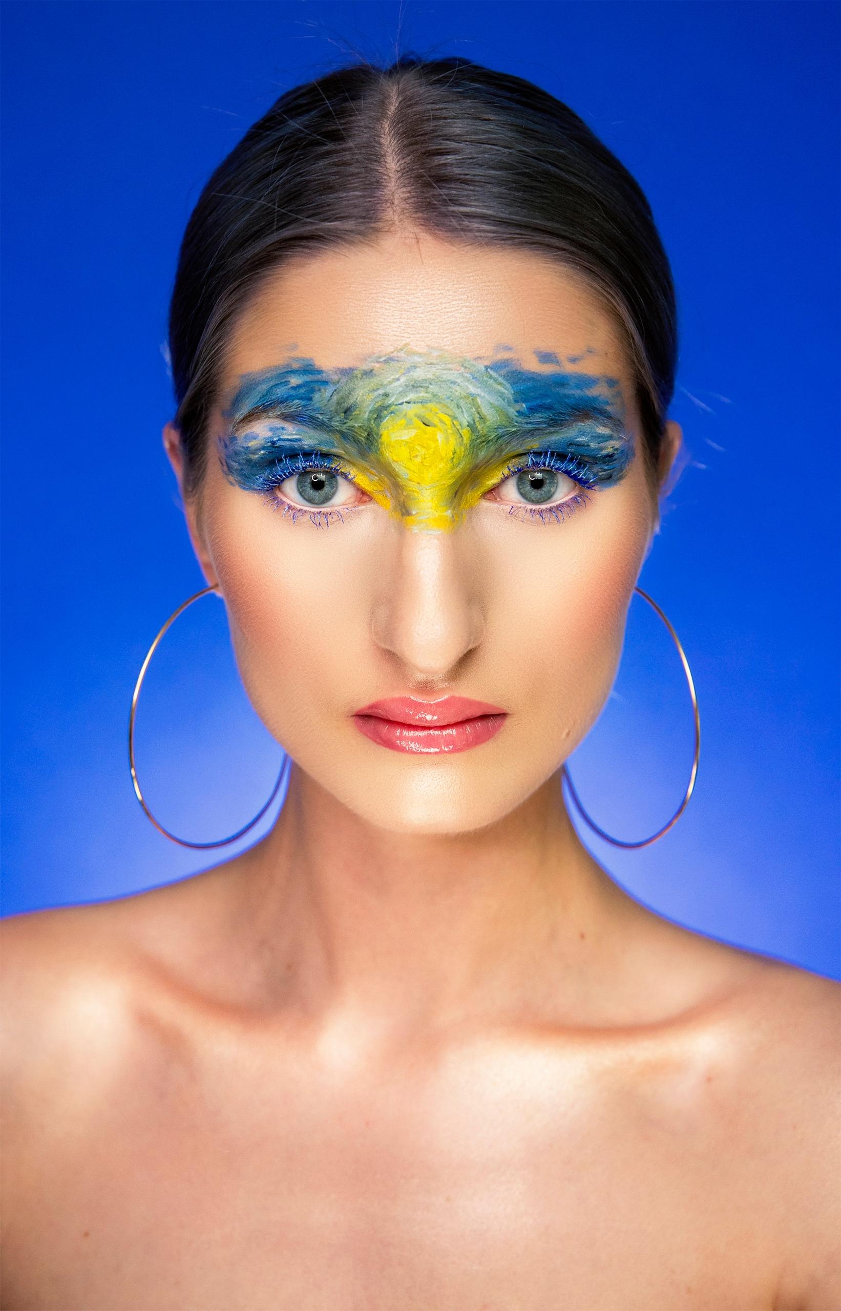 Fotografia przedstawia portret kobiety w artystycznym makijażu na niebieskim tle. Kobieta ma związane włosy i lekko pochyloną głowę.